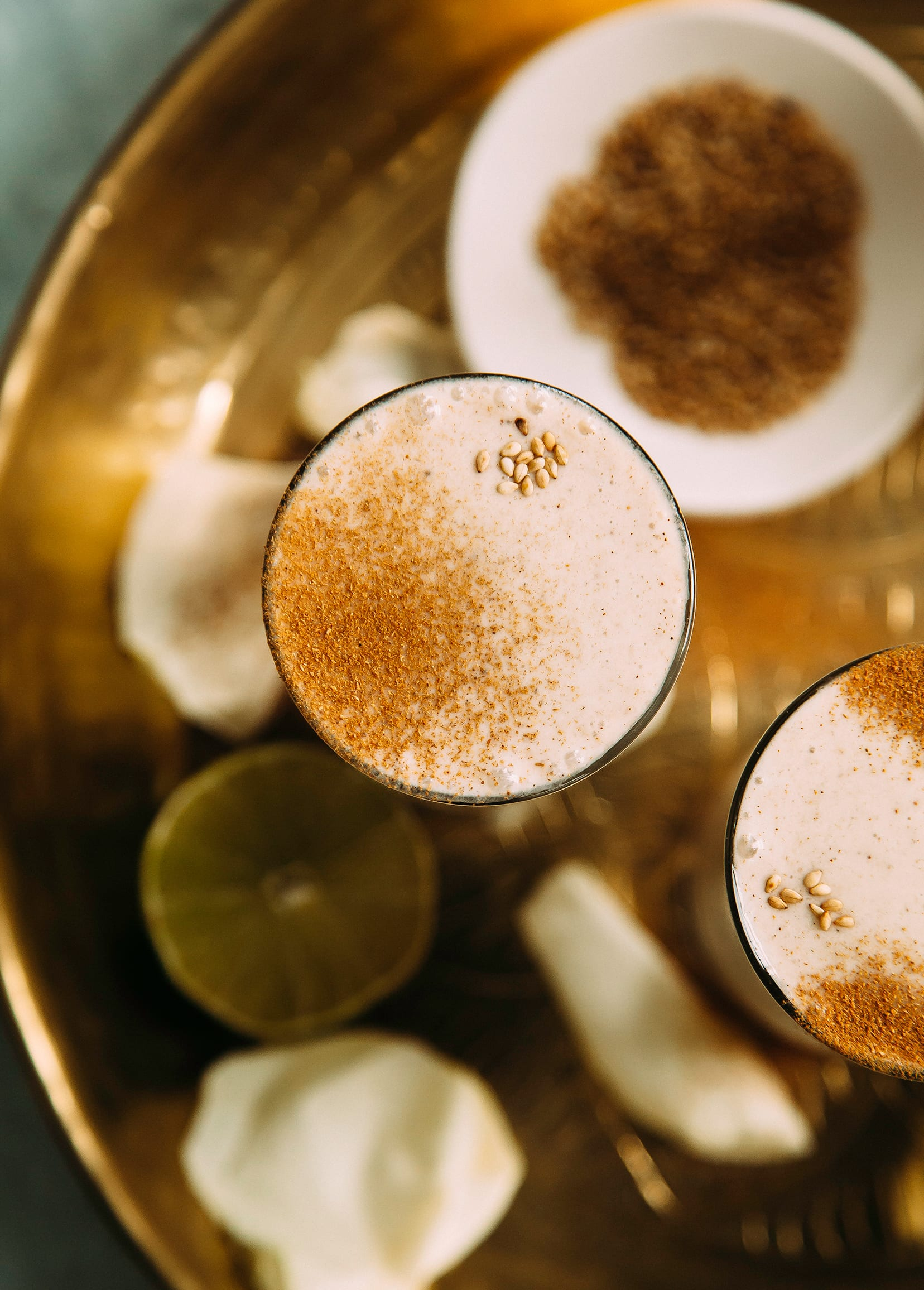 An overhead and up close shot of a creamy beige beverage in a slim clear glass beverage on top of a gold, etched tray. The beverage is garnished with ground cinnamon and sesame seeds.