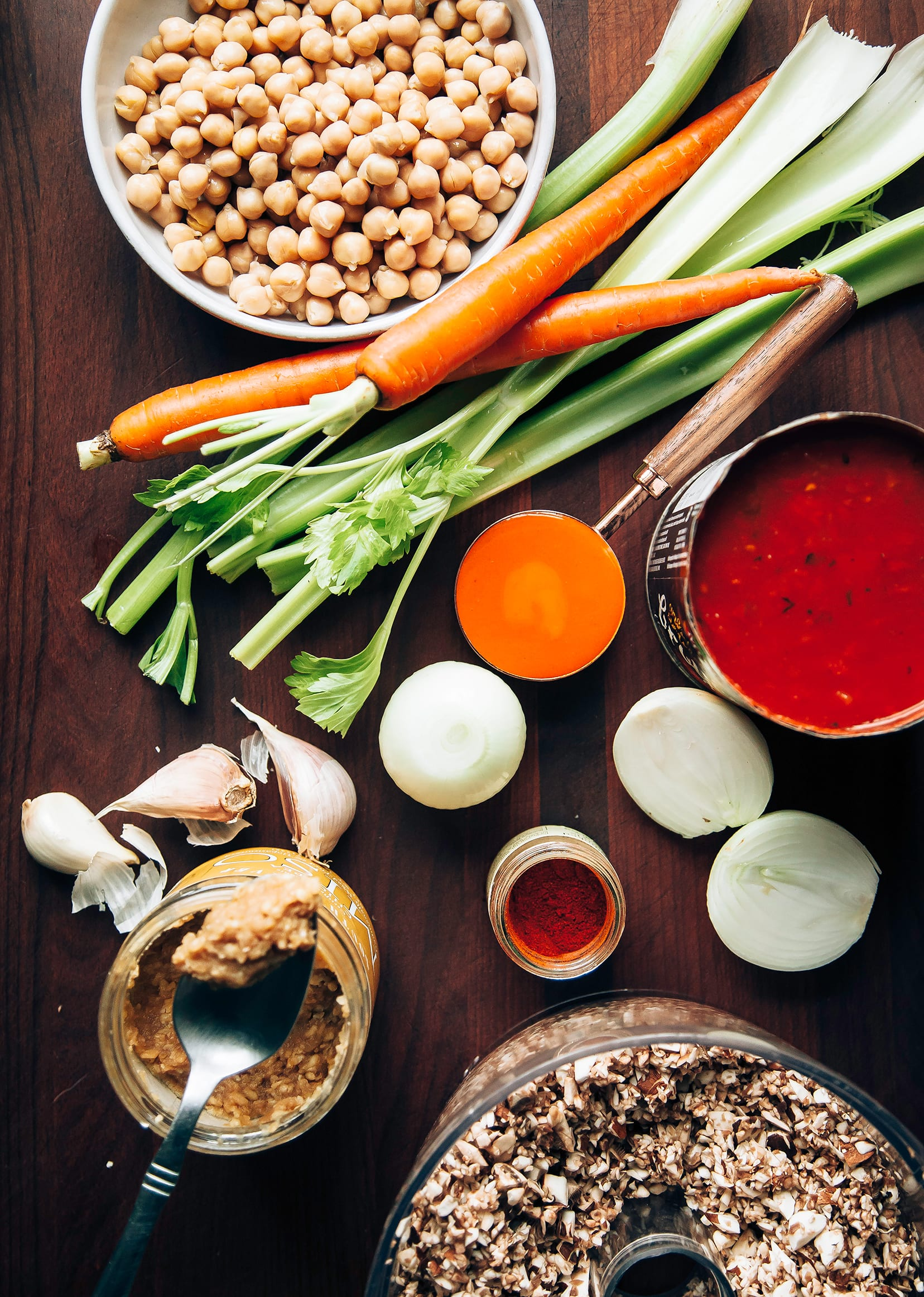 An overhead shot of ingredients for a Buffalo chickpea chili on a dark wood background.