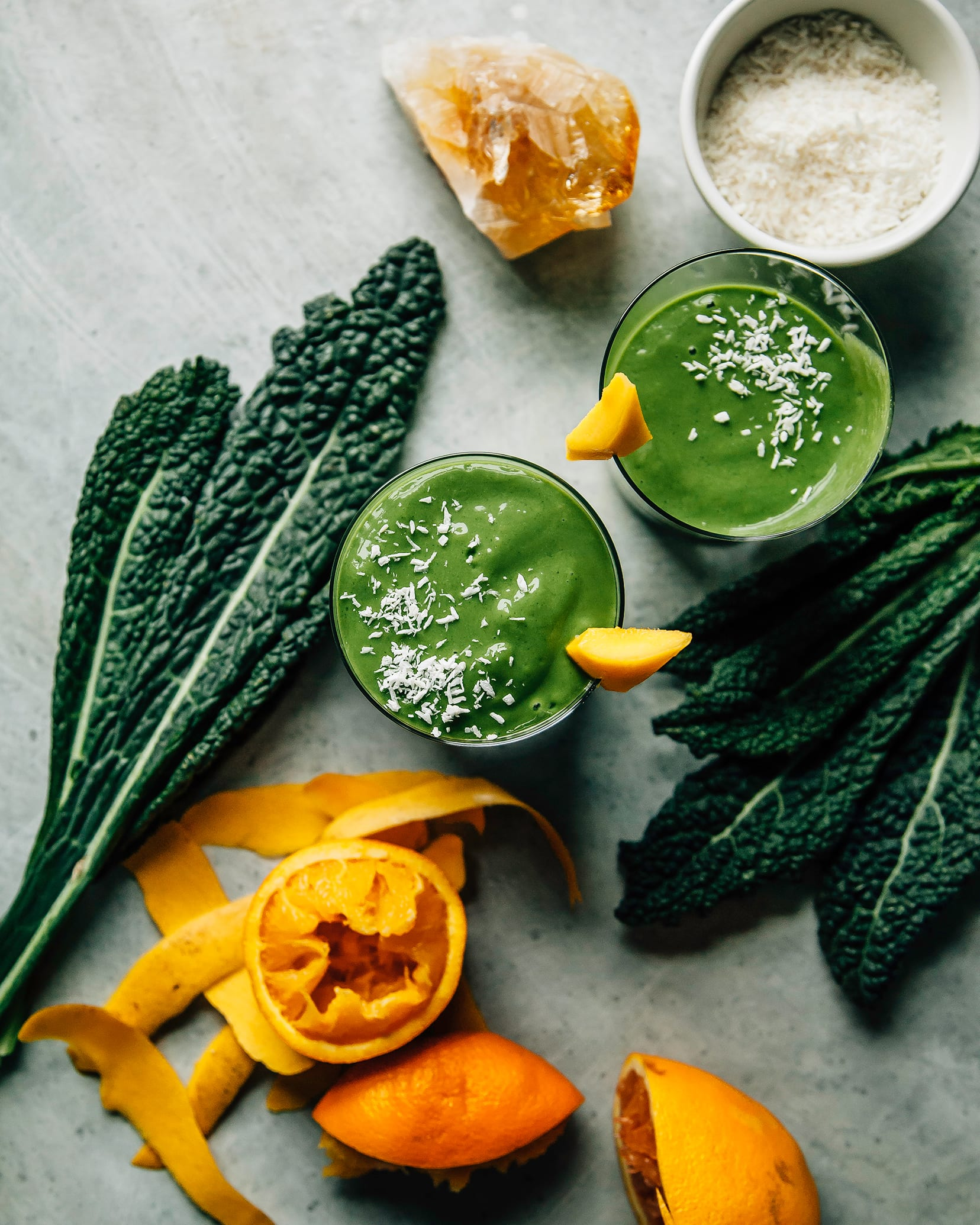 Overhead shot of 2 deep green smoothies in clear glasses on a light blue background. Kale leaves and squeezed oranges are nearby. The smoothies are garnished with shredded coconut and a piece of mango is perched on the rim of the glasses.