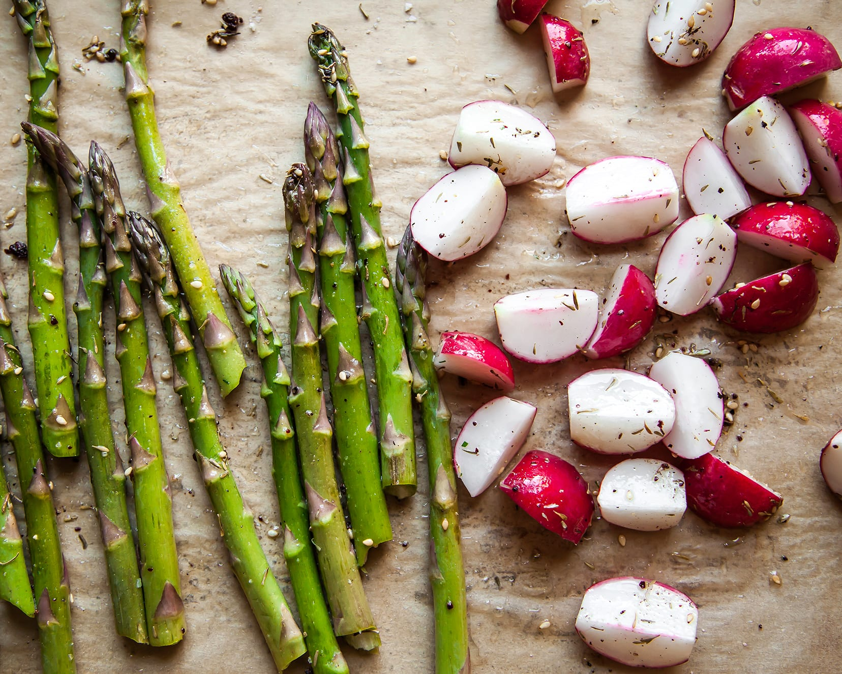 Image shows roasted asparagus and radishes on top of brown parchment paper.