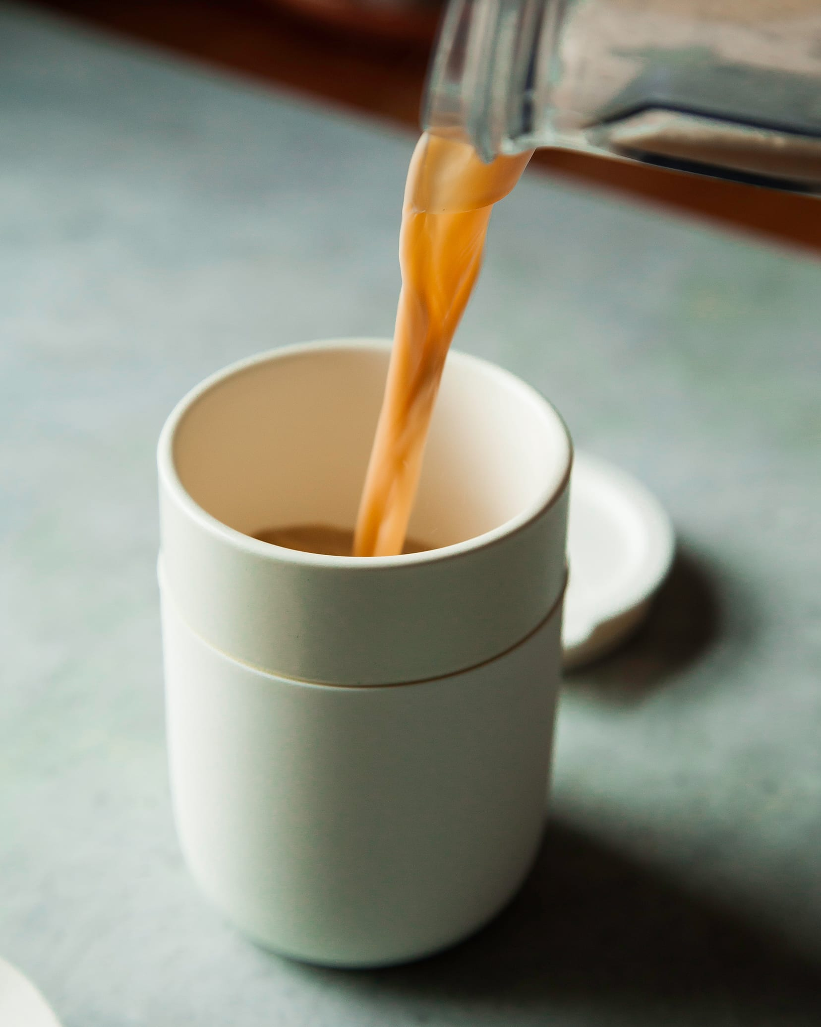 A tea latte is being poured into a white to-go mug.
