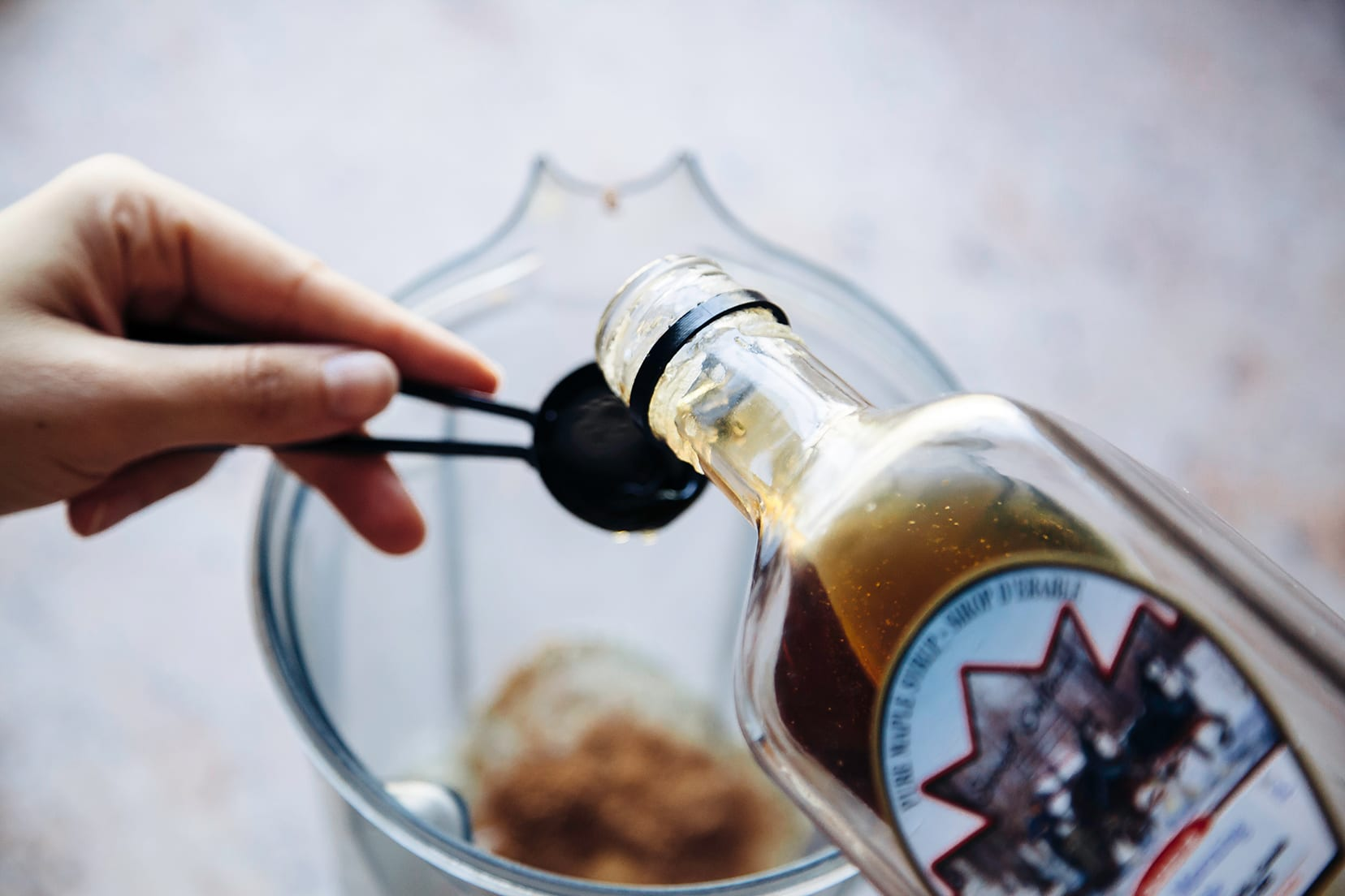 An up close shot of a hand pouring maple syrup into a measuring spoon.