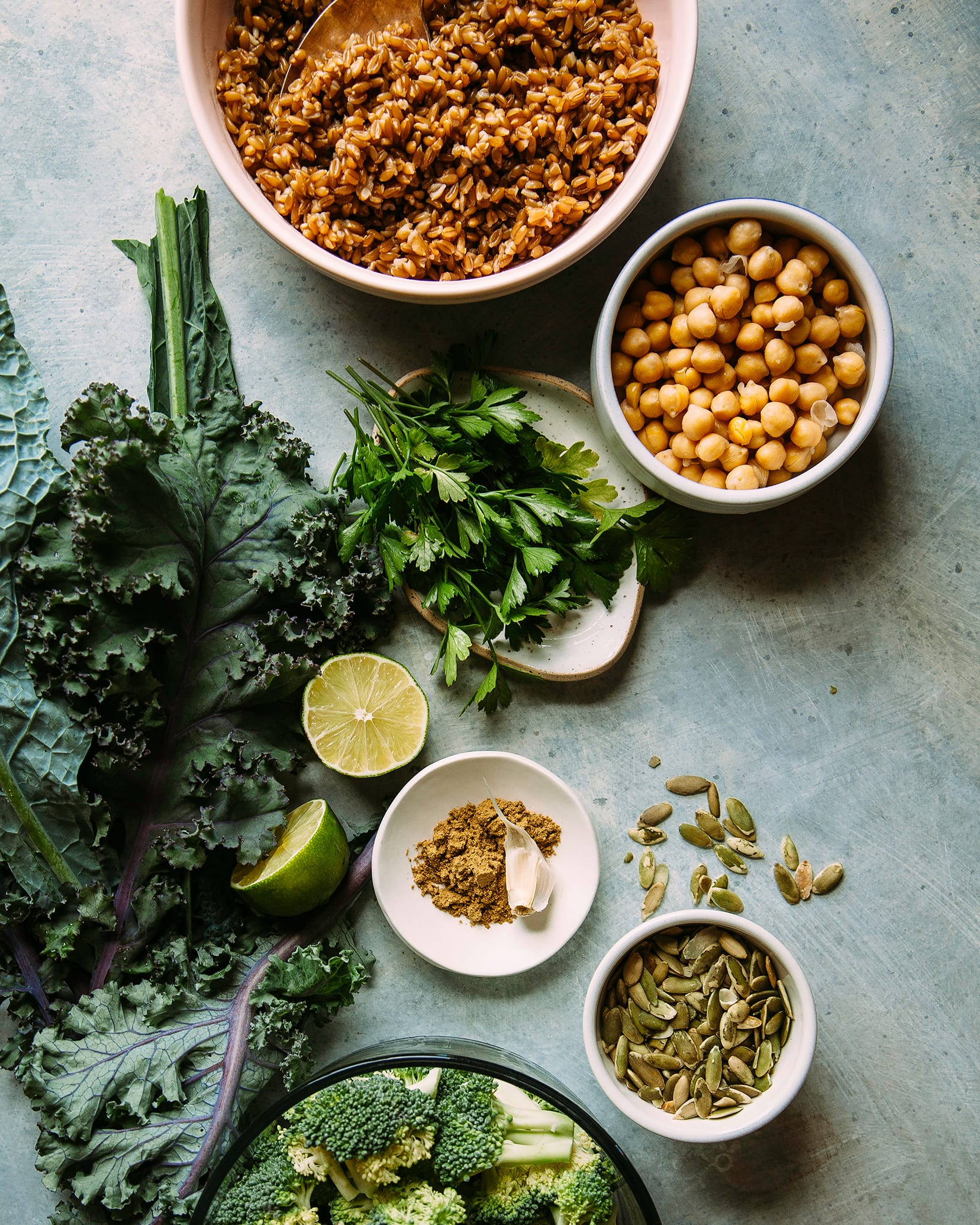 An overhead shot of ingredients for vegan green goddess bowls over a blue background.