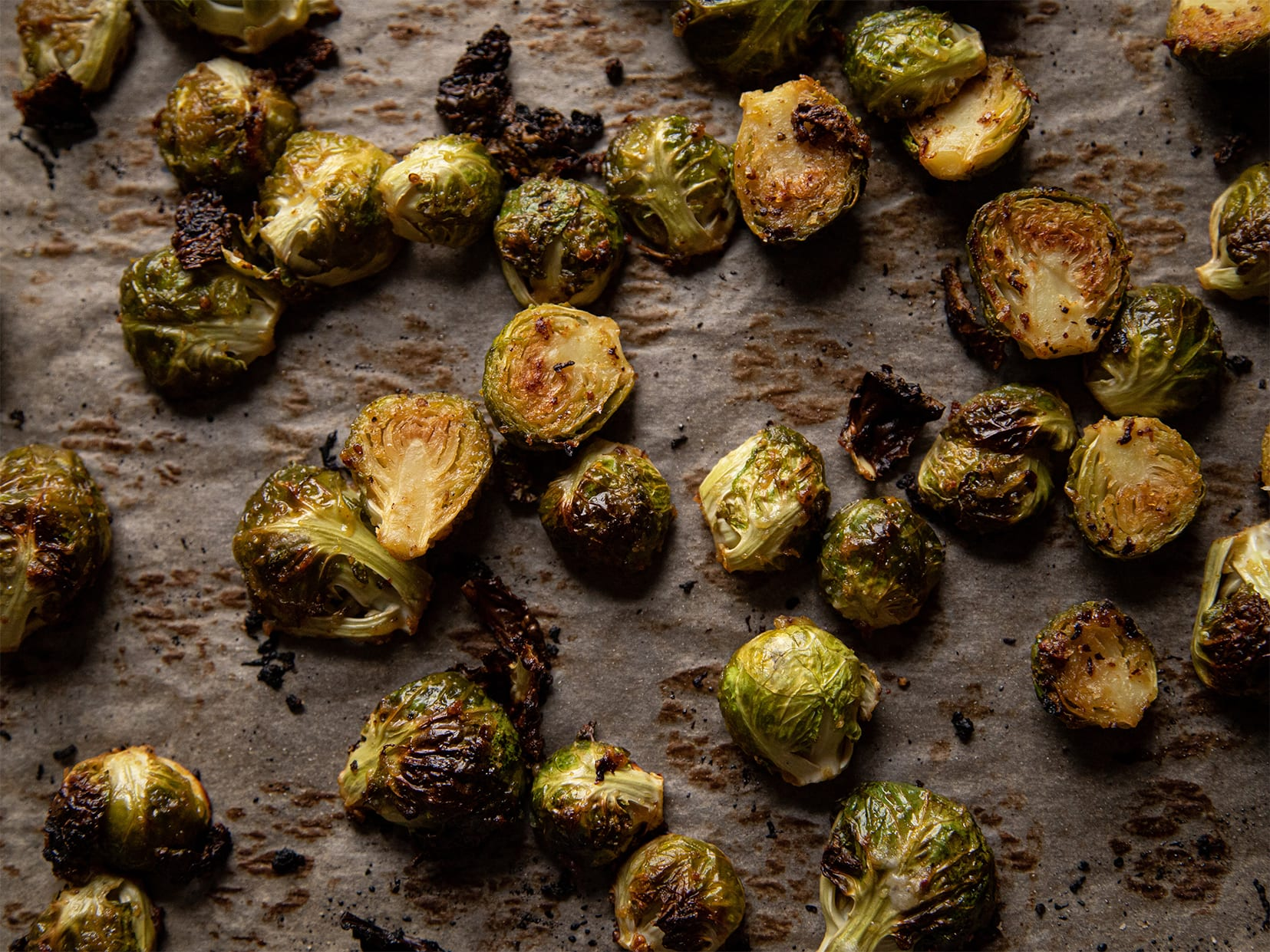 A tray of roasted Brussels sprouts, up close with moody lighting.