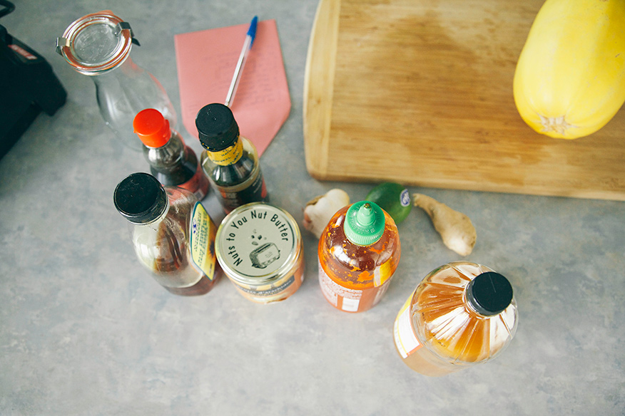 An overhead shot of jars of ingredients for peanut sauce on a naturally lit grey countertop.
