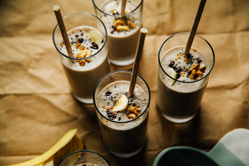 An overhead shot of several banana bread shakes in slim glasses on a brown paper background. Shakes are garnished with sliced banana, walnuts, and cacao nibs and finished with beige paper straws.