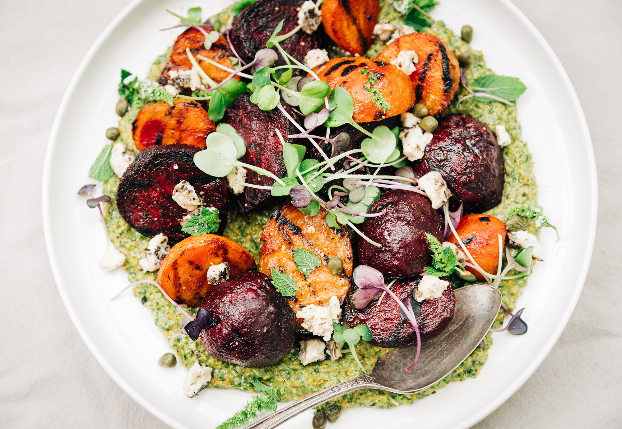 An overhead shot of some grilled beets on top of a textured green sauce on a white plate. The dish is garnished with purple and green radish micro greens and small bits of creamy white vegan cheese.