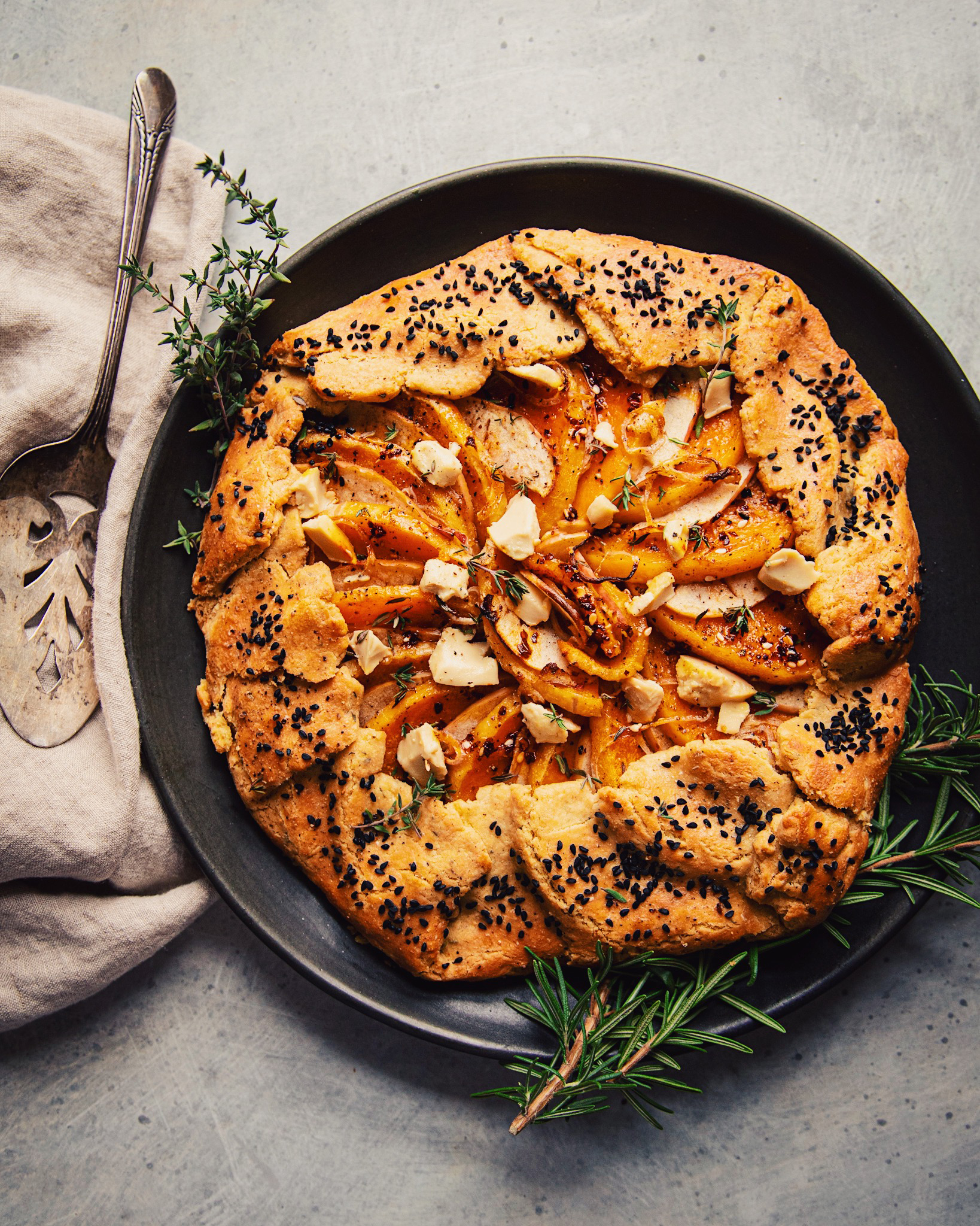 An overhead view of a vegan butternut patty on a matte black plate against a mottled gray background.  It is garnished with sprigs of thyme and rosemary.  There is a beige and antique linen pie tray on the side.