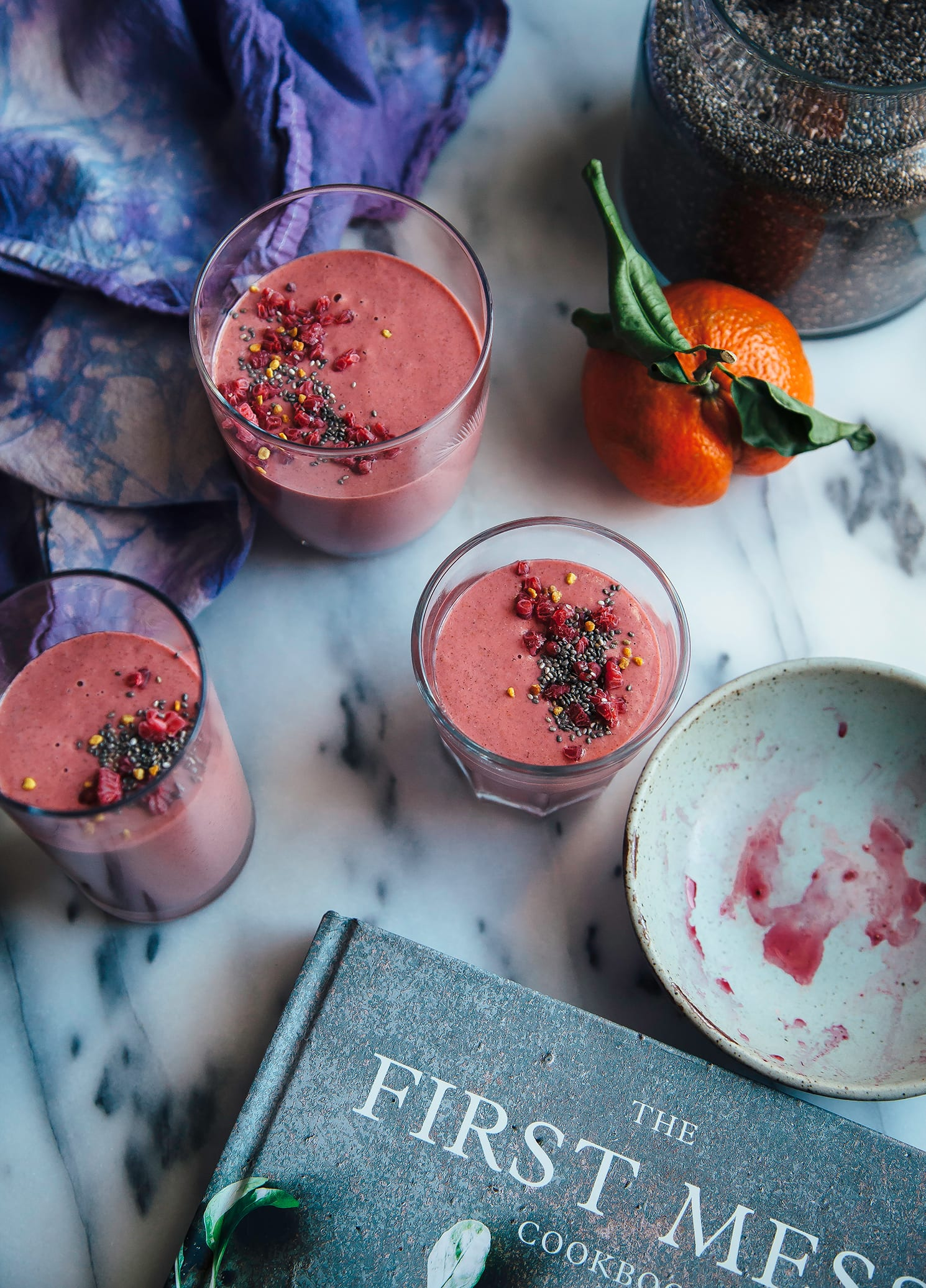 Overhead shot of a pink smoothie served in 3 glasses with The First Mess cookbook shown to the side.
