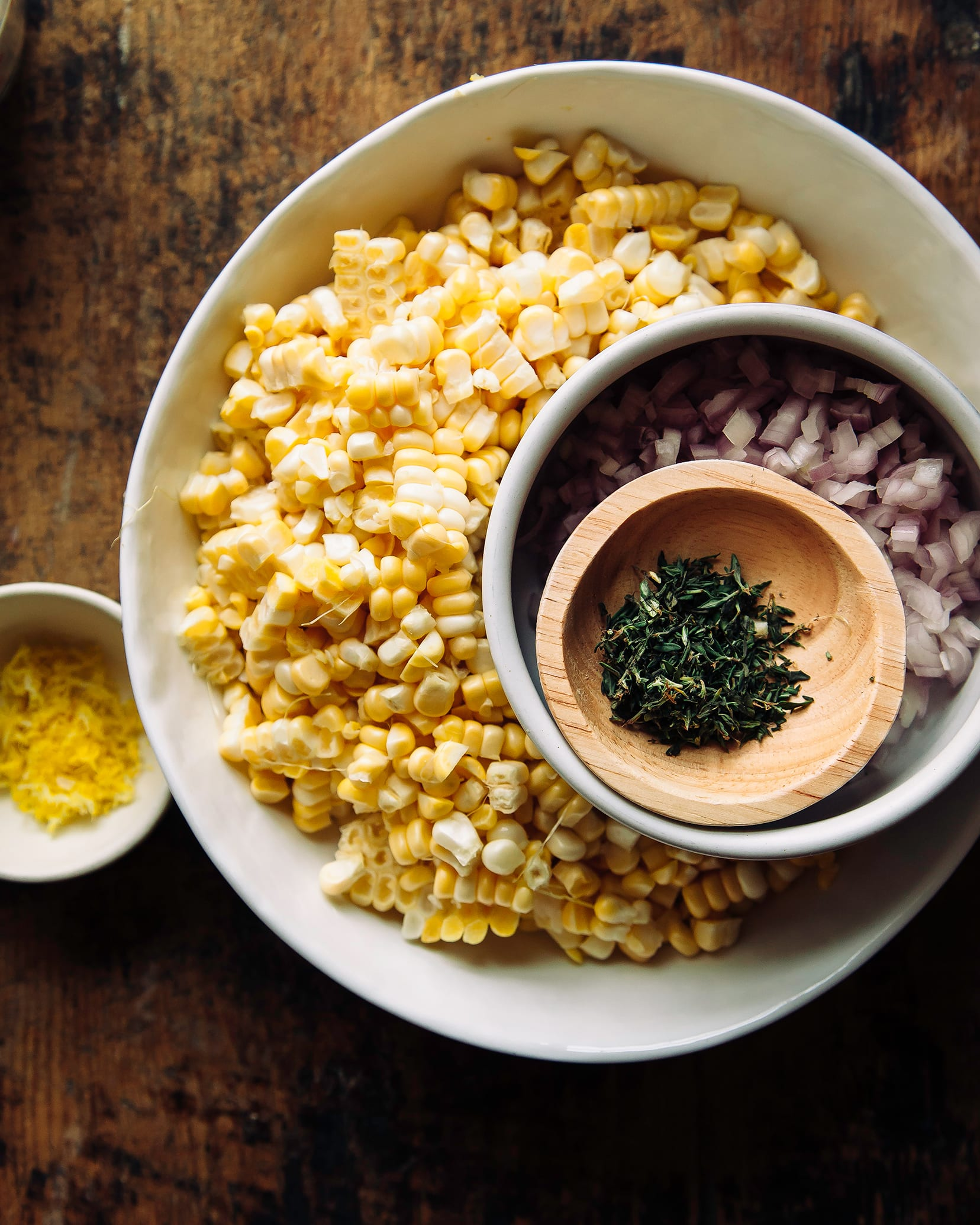 An overhead shot of prepped ingredients in bowls over a worn wooden background.