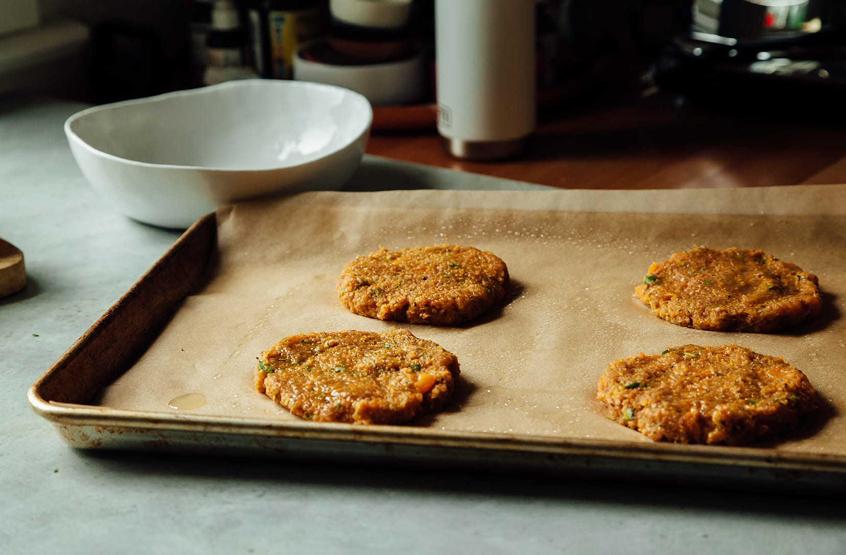 A 3/4 angle shot of formed sweet potato cake patties on a parchment lined baking sheet.