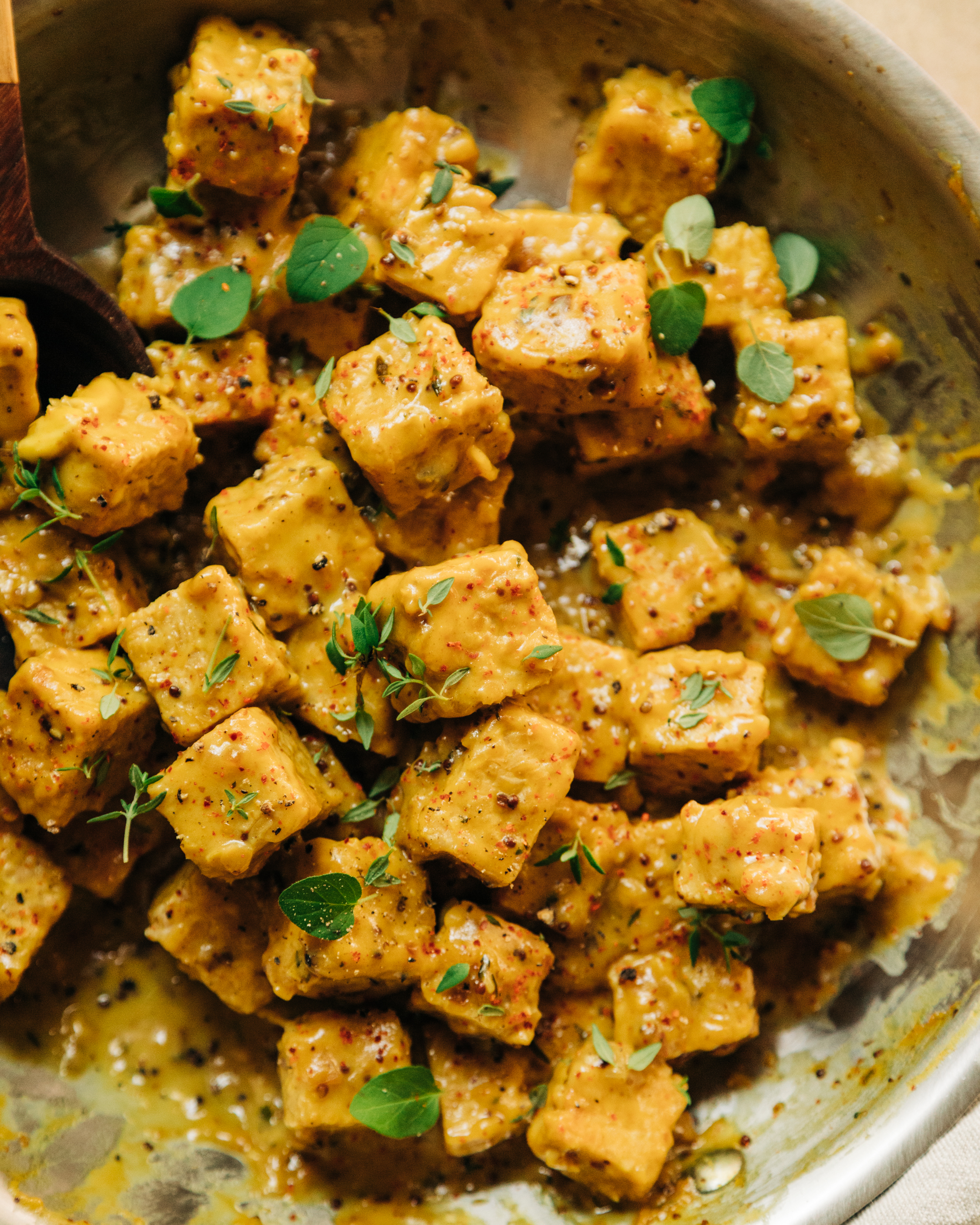 An up close, overhead shot of saucy chunks of maple mustard tempeh in a skillet. The sauce is golden yellow and the tempeh is garnished with fresh thyme and oregano leaves.