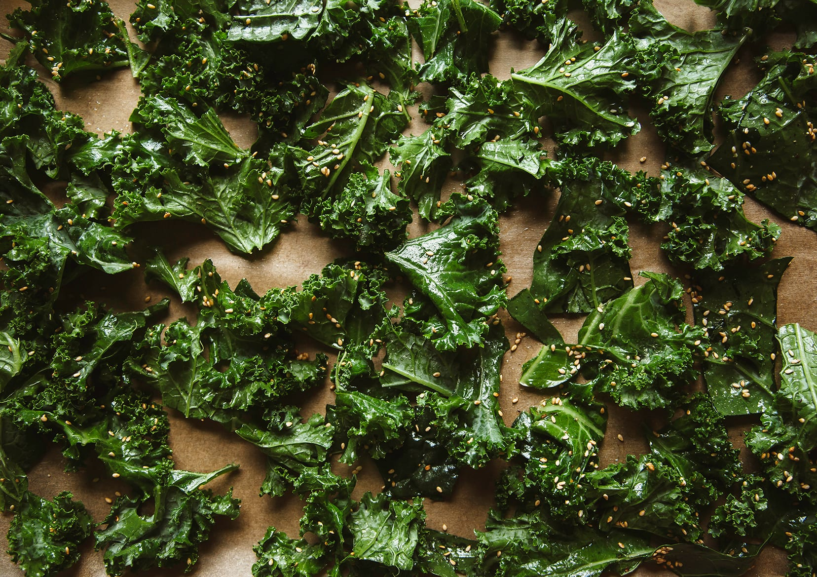 Image shows a bunch of kale leaves coated in oil, before roasting.