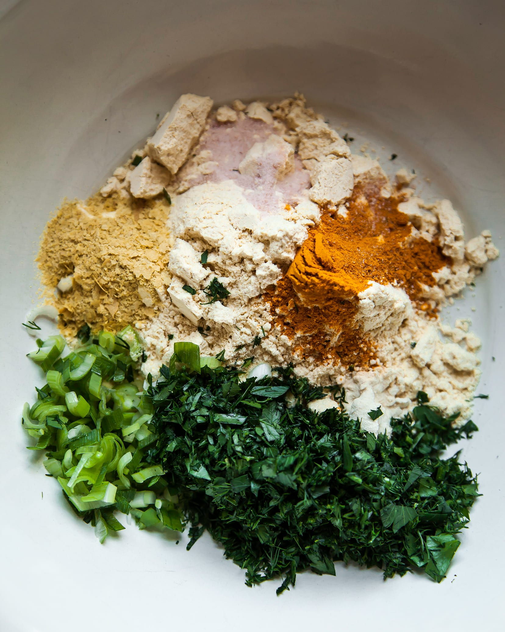 Image is an overhead shot of chickpea flour, herbs, and spices in a bowl.
