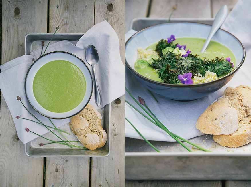 Two images show a bowl of mellow and creamy green asparagus soup. The osup is garnished with kale chips and violet flowers. There are slices of bread to the side.