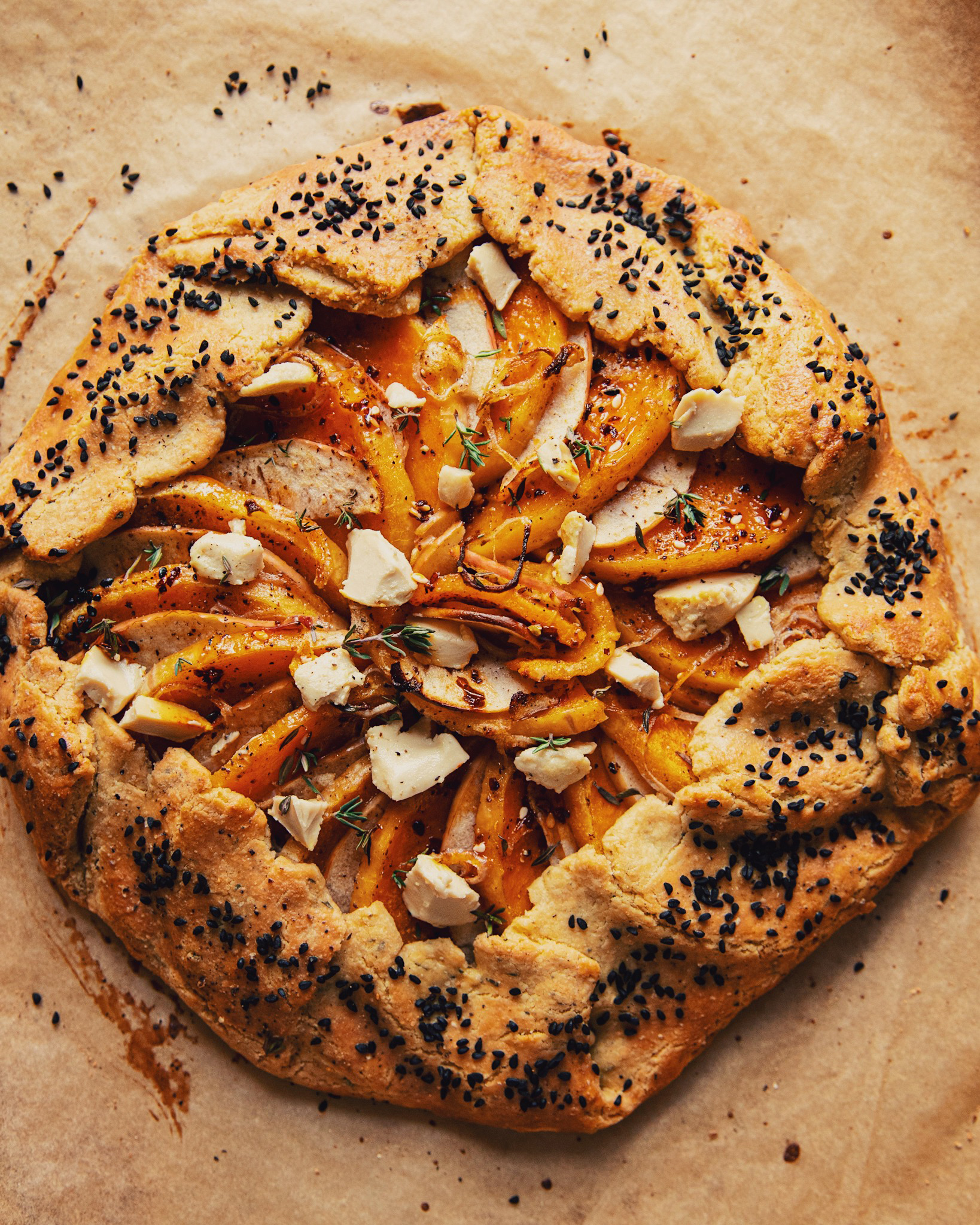 An overhead shot of a vegan butternut galette with apples, shallots, Dijon mustard, and gluten-free black pepper crust.