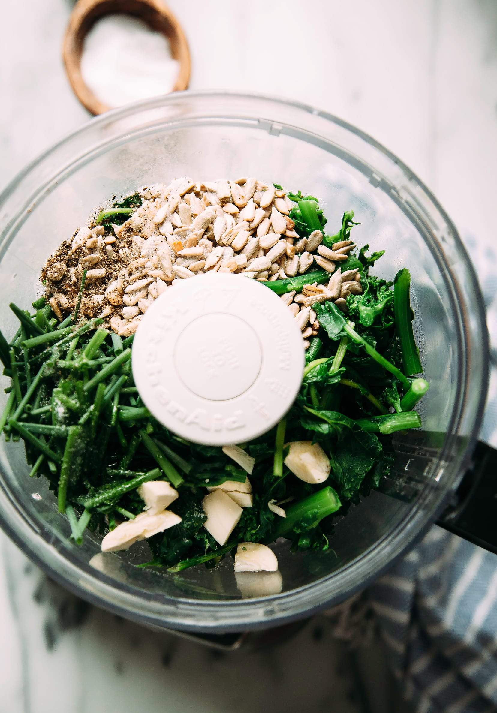 Image shows a food processor filled with ingredients for a broccoli rabe and chive pesto.