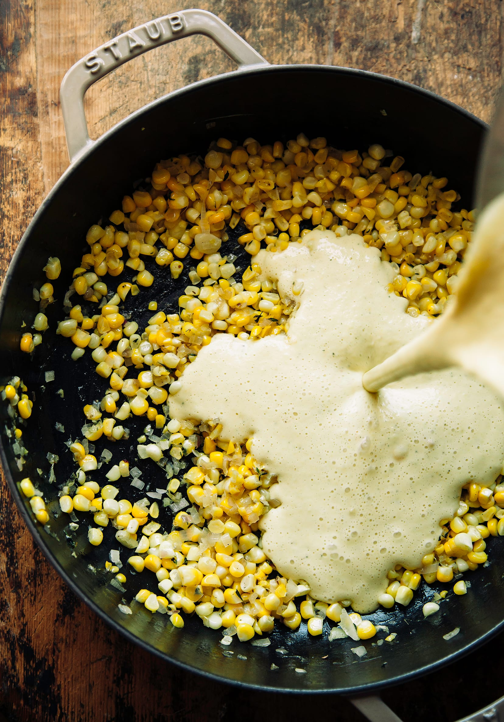 """A vegan """"cream"""" is added to a braiser-style pot that has cooked corn inside."""