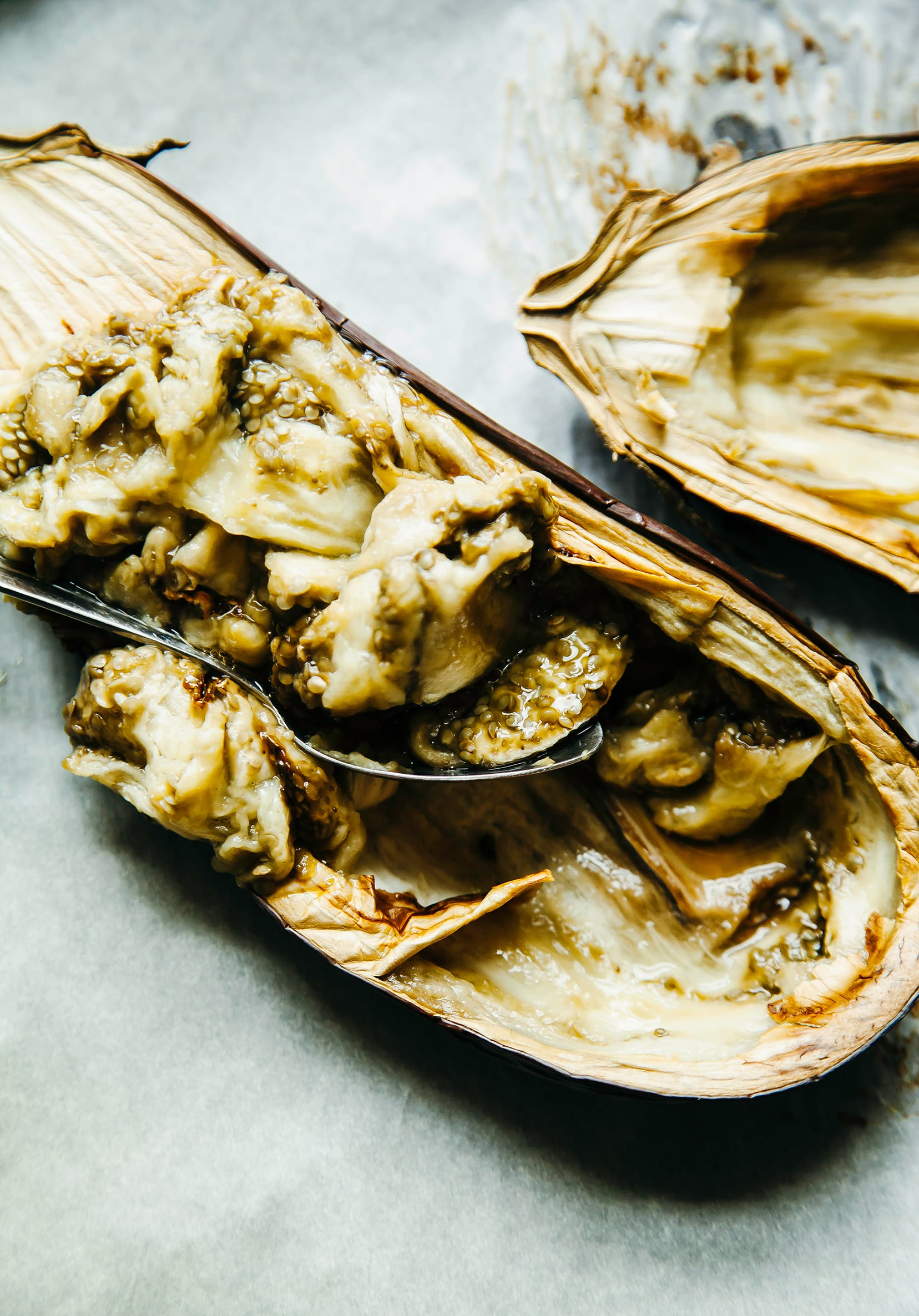 Image shows roasted eggplant halves being scooped out by a spoon.