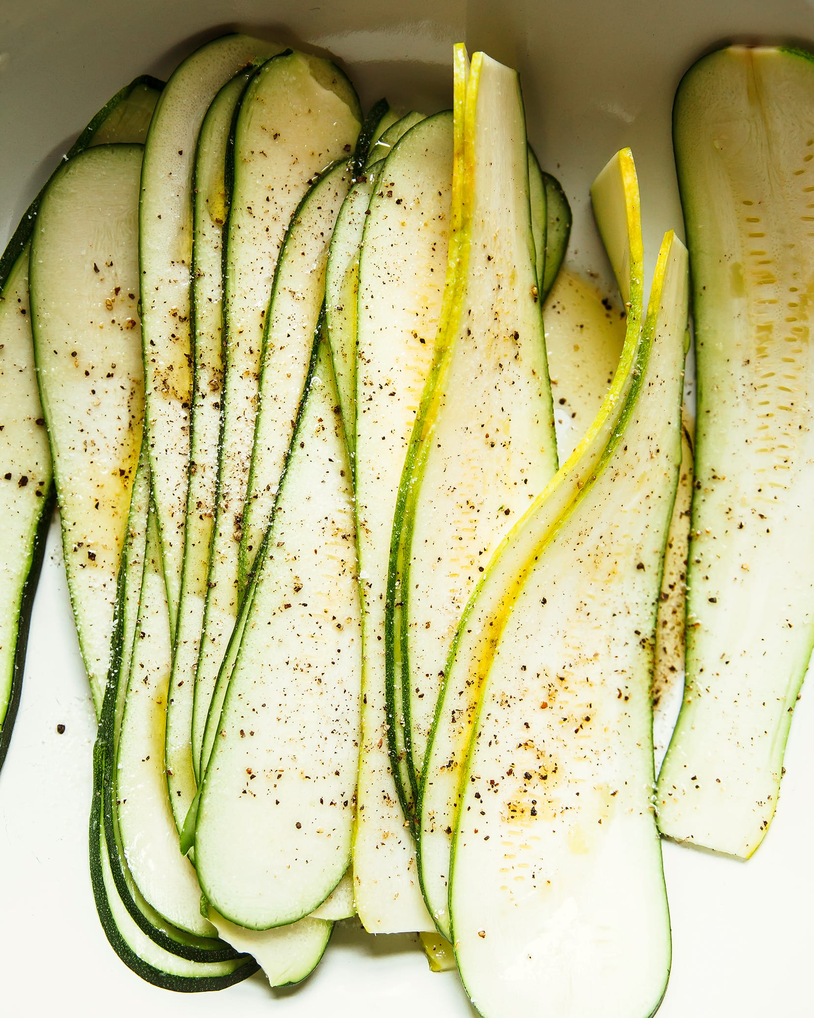 An overhead shot of very thin zucchini slices, seasoned with salt and pepper.