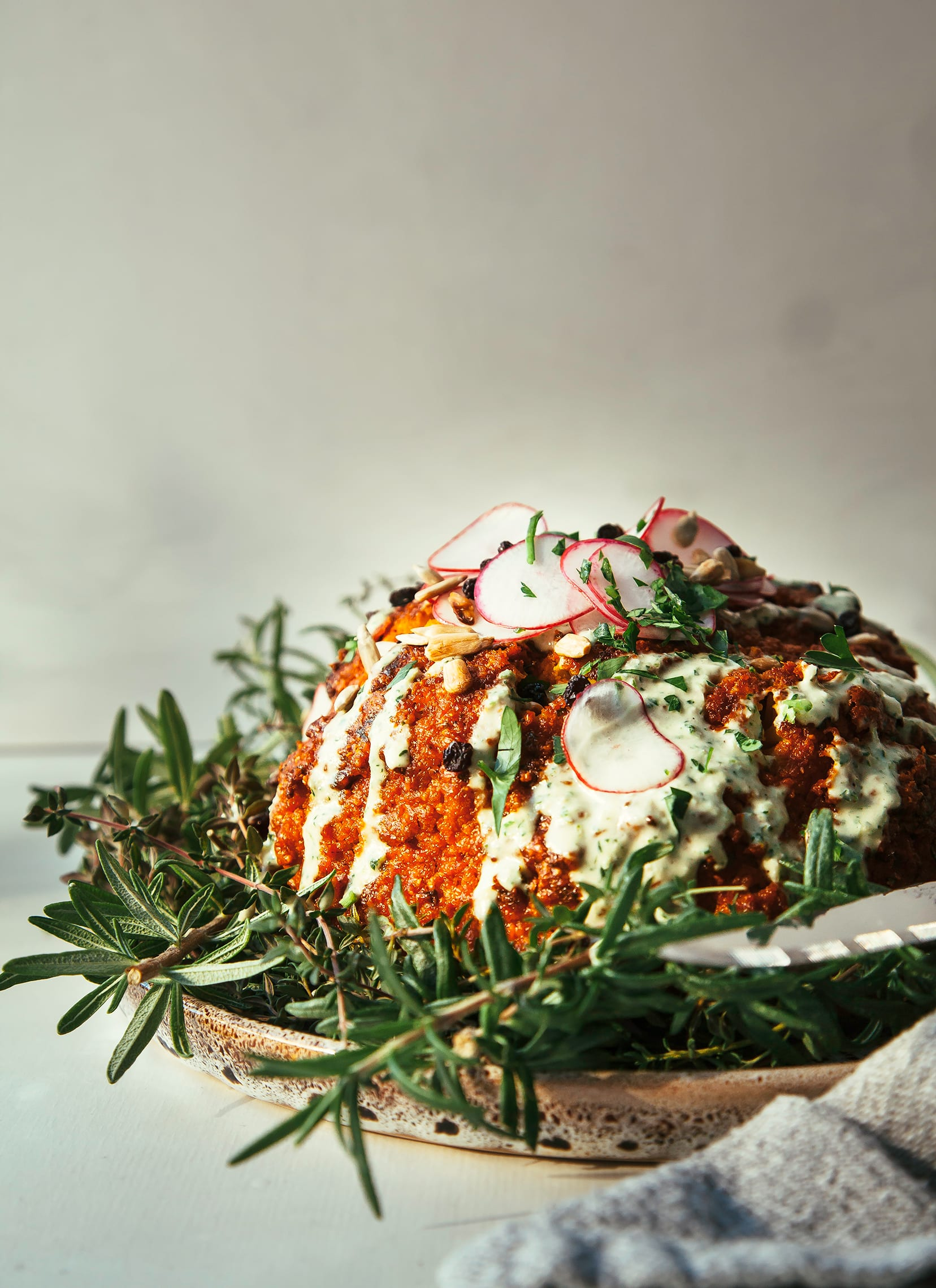 ROMESCO ROASTED WHOLE CAULIFLOWER w/ HERBED TAHINI CREAM - The First Mess
