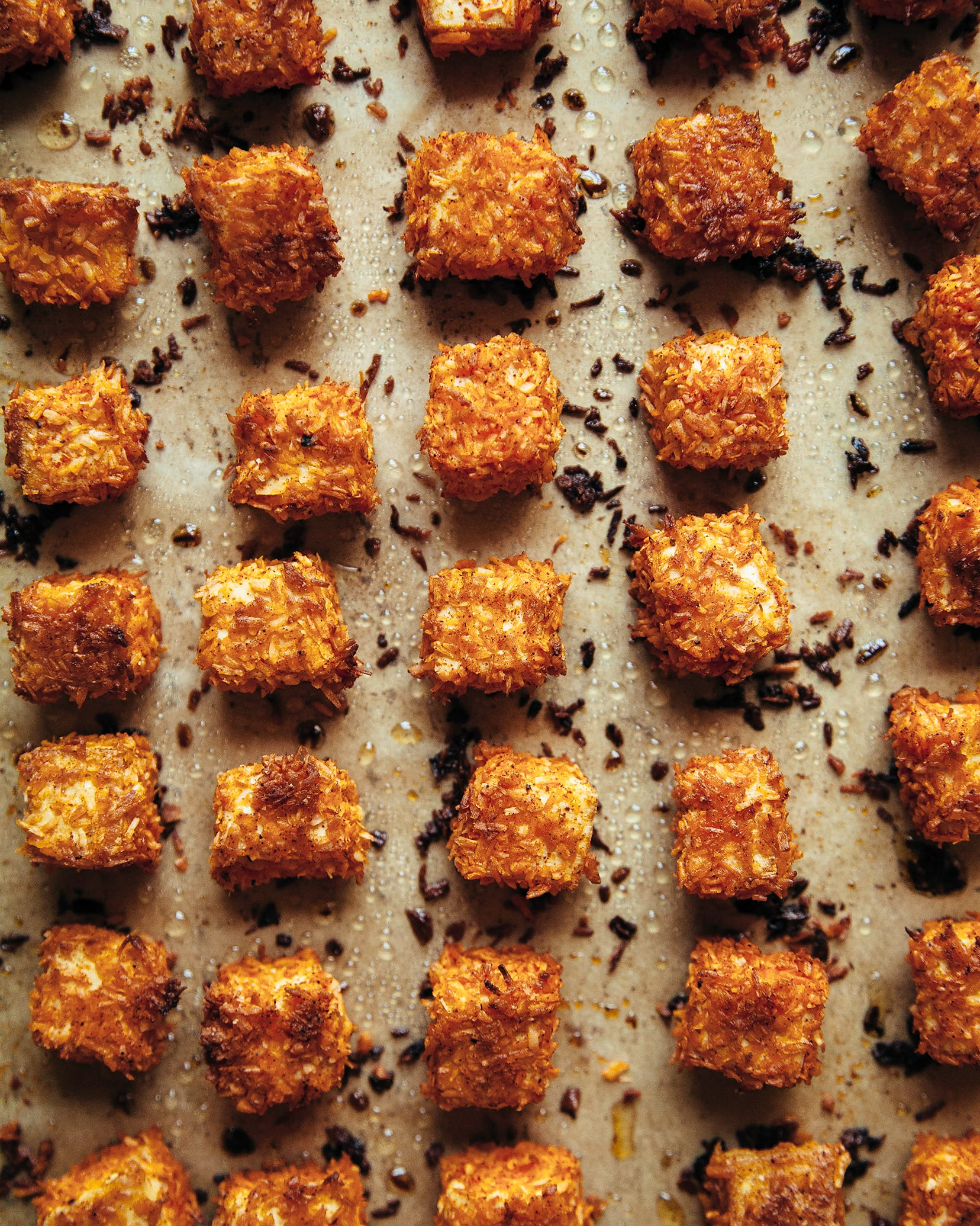 An overhead shot of crispy coconut tofu after baking, on a parchment lined baking sheet.