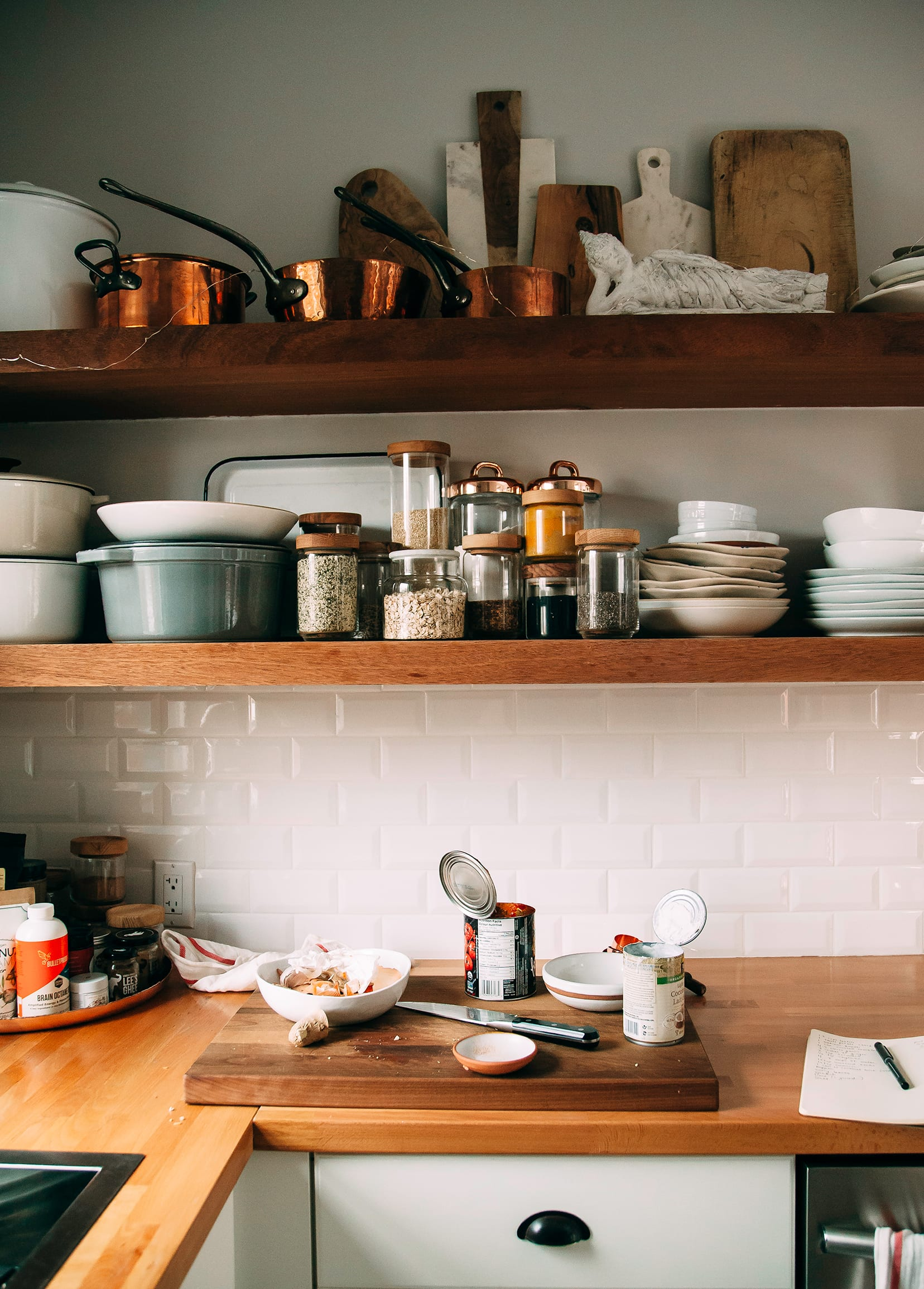 Image shows a kitchen scene with open shelving and canned ingredients open on the counter.
