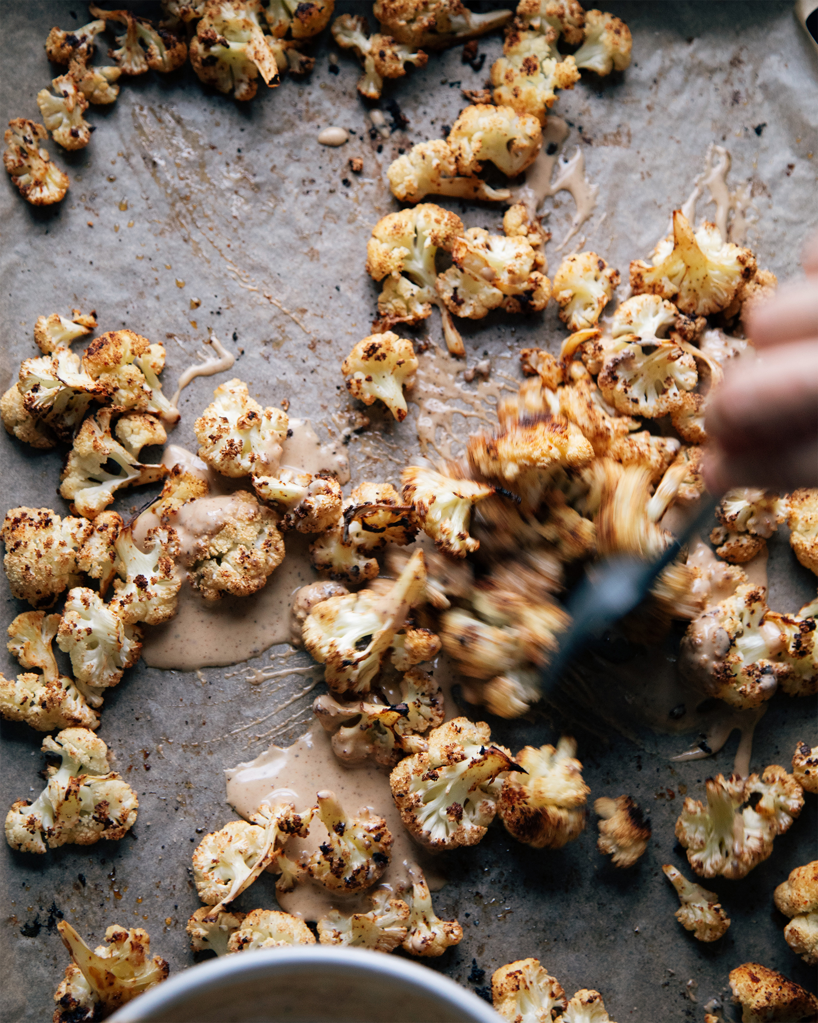 Tossing the cauliflower on a sheet pan.