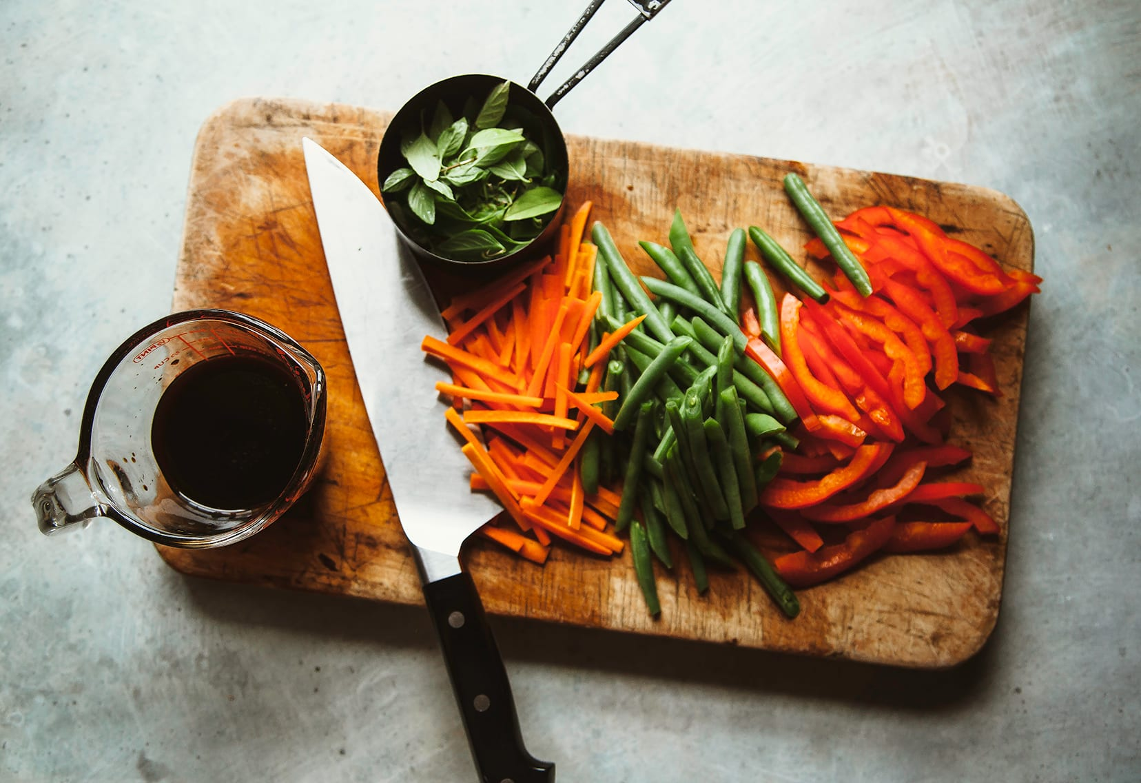 Image shows sliced vegetables on a cutting board along with a cup of Thai basil leaves.
