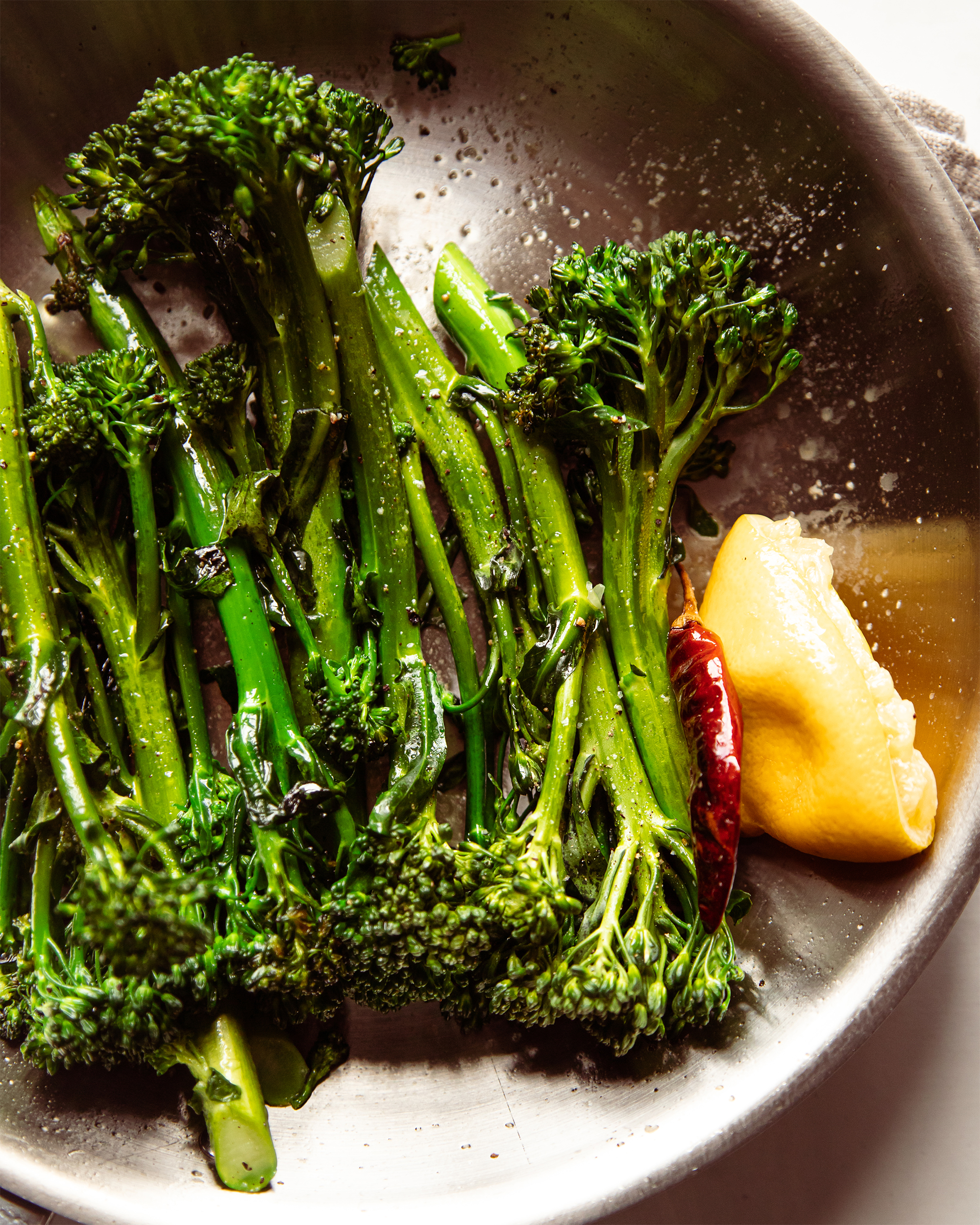An overhead shot of cooked broccolini in a pan.