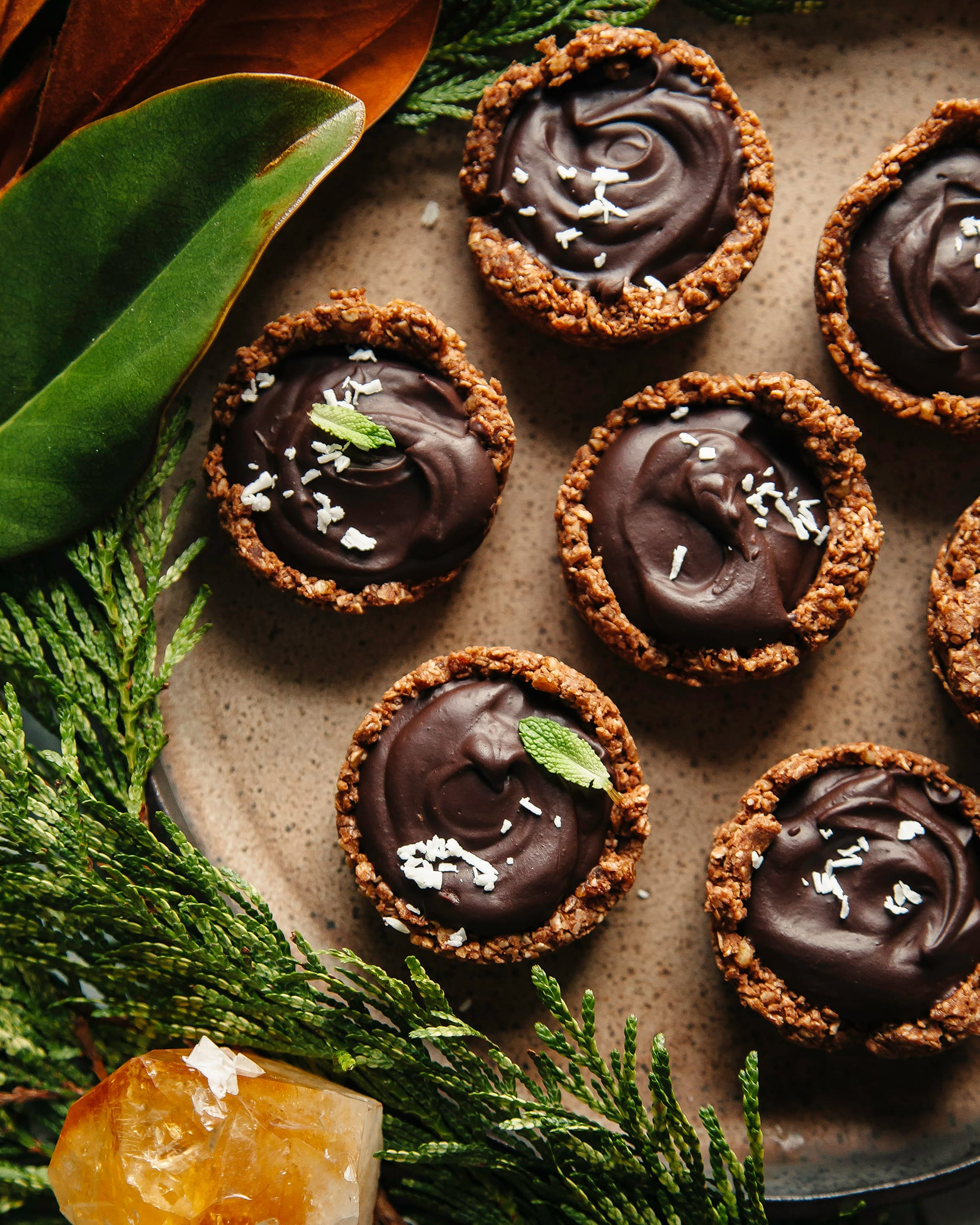 An overhead shot of chocolate ganache cups on a brown plate.
