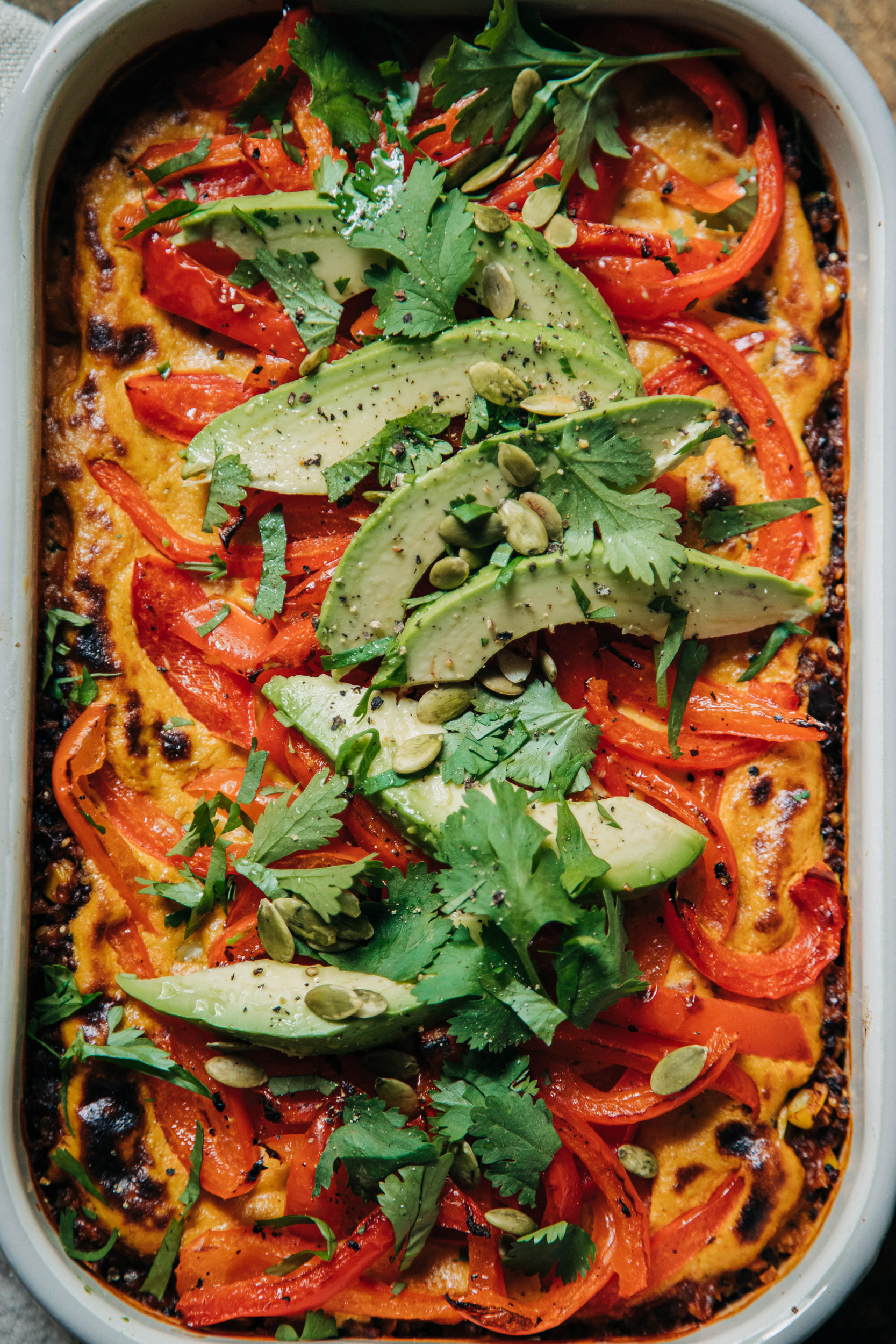 An overhead shot of a vegan casserole topped with sautéed bell peppers, avocado, and chopped cilantro. The casserole dish is white.