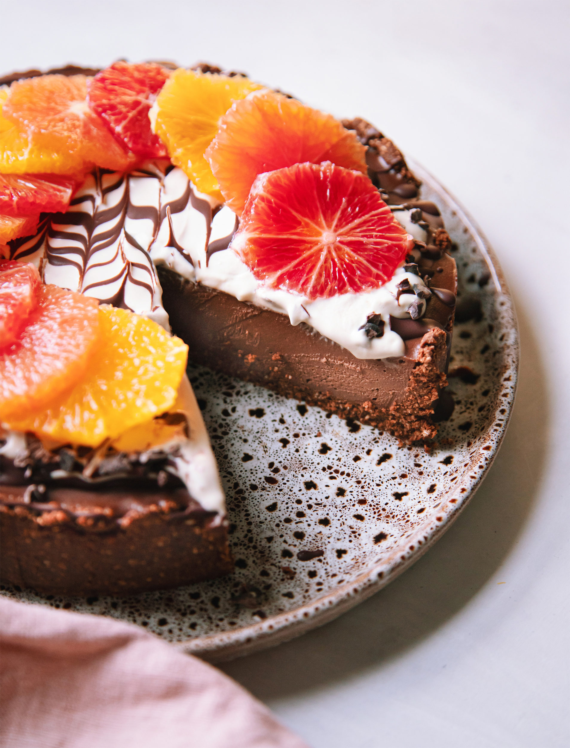 A side angle shot of a vegan chocolate orange cheesecake with a slice removed, showing the chocolaty truffle-like texture of the cake. The top of the cheesecake is decorated with different coloured orange slices and a bright white cashew cream marbled with melted chocolate.