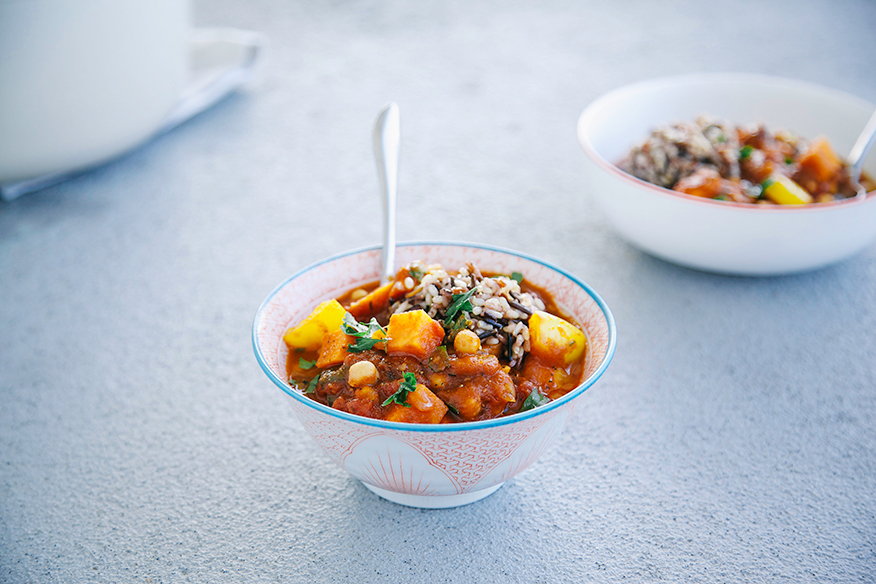 Side angle shot of vegetable and chickpea stew on a light grey background.
