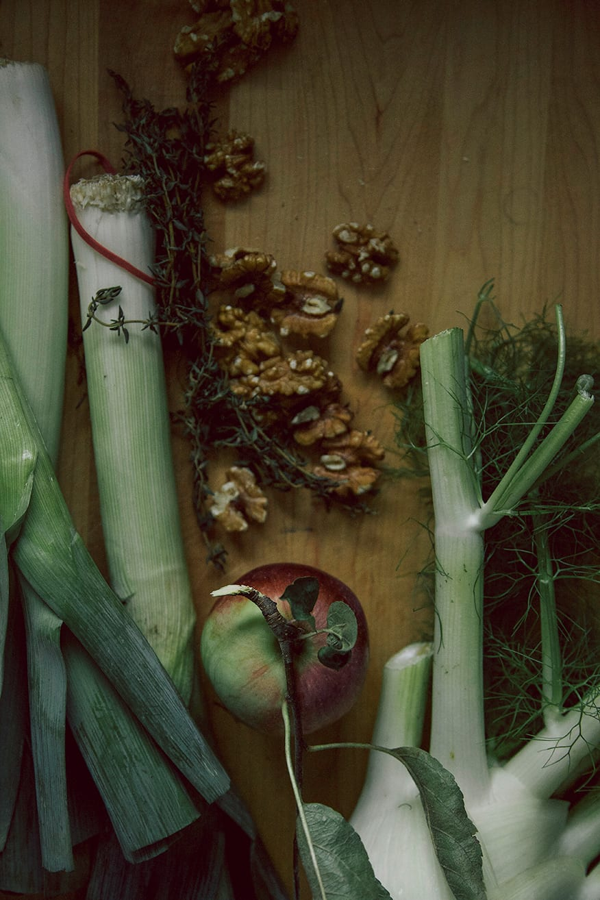 An overhead shot of soup ingredients on a light wood cutting board in moody lighting.