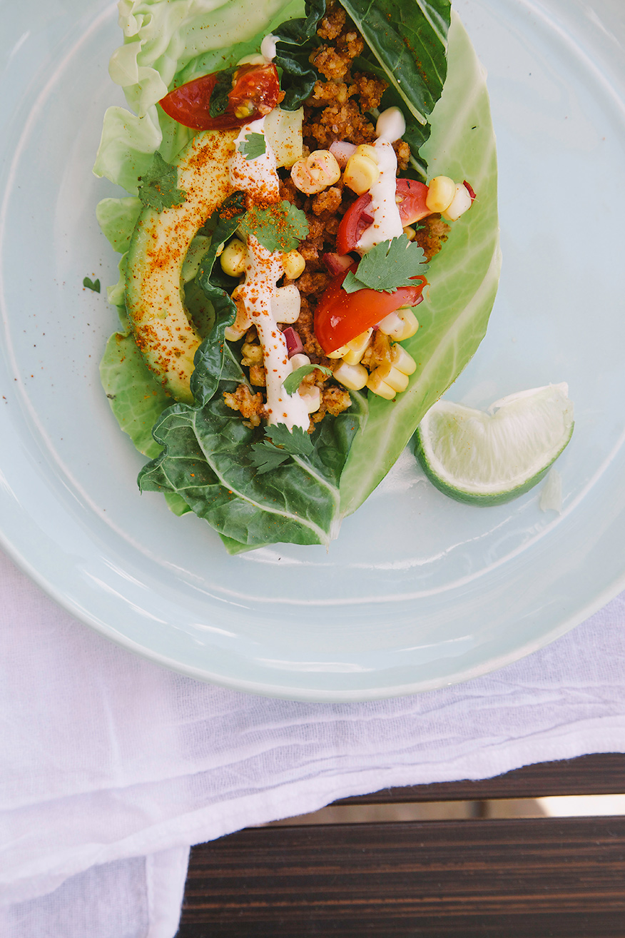 "An overhead shot of a raw and vegan taco inside of a cabbage leaf on top of a light blue plate. The taco features ground up spiced walnut ""meat,"" corn salsa, a slice of avocado and a bright white squiggle of cashew sour cream."