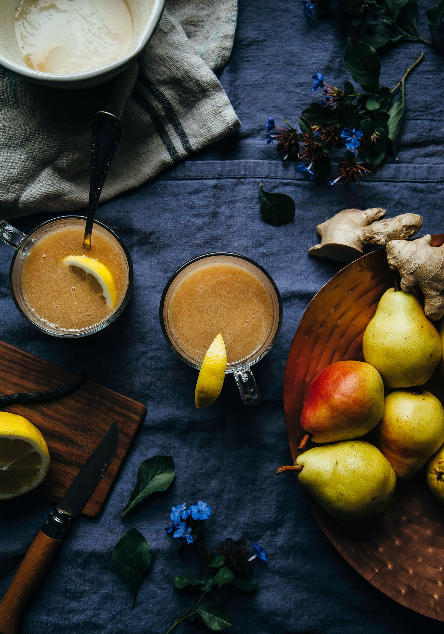 An overhead shot of warm cider in 2 clear mugs. Pears, ginger root, and a halved lemon are seen to the side.