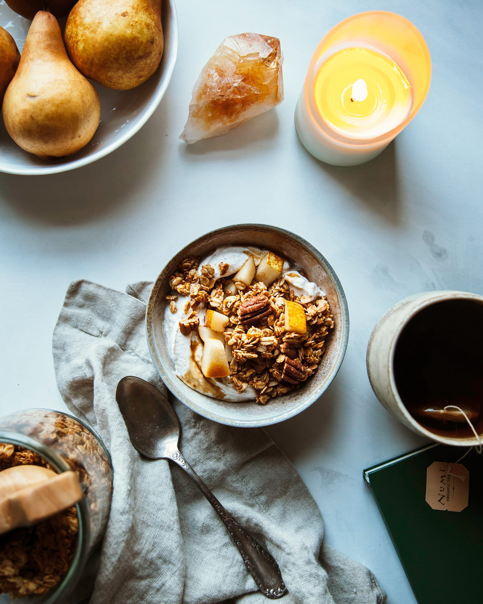 Overhead shot of sweet potato granola in a bowl with chopped pear and coconut milk granola. There is a lit candle to the side and a bowl of Bosc pears and a cup of tea.