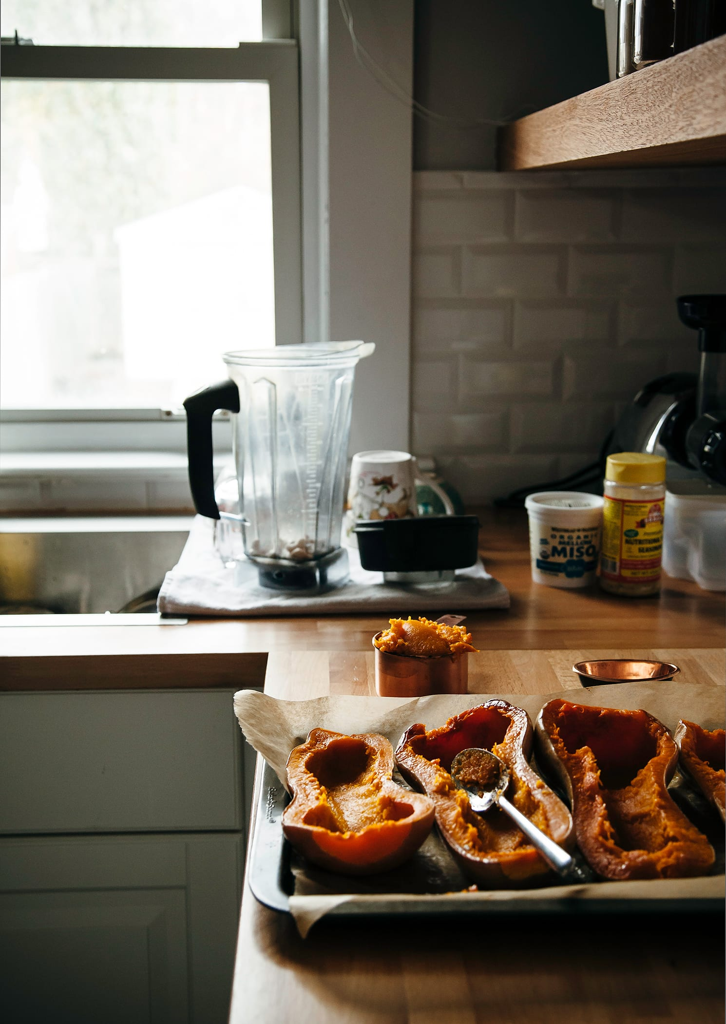 A kitchen scene shows a tray of roasted butternut squash halves and a blender pitcher on the counter.
