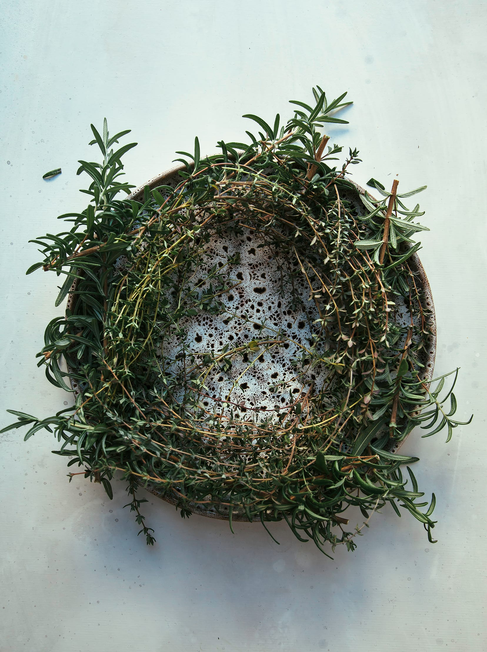 """Image shows a """"wreath"""" made out of thyme and rosemary on top of a plate."""
