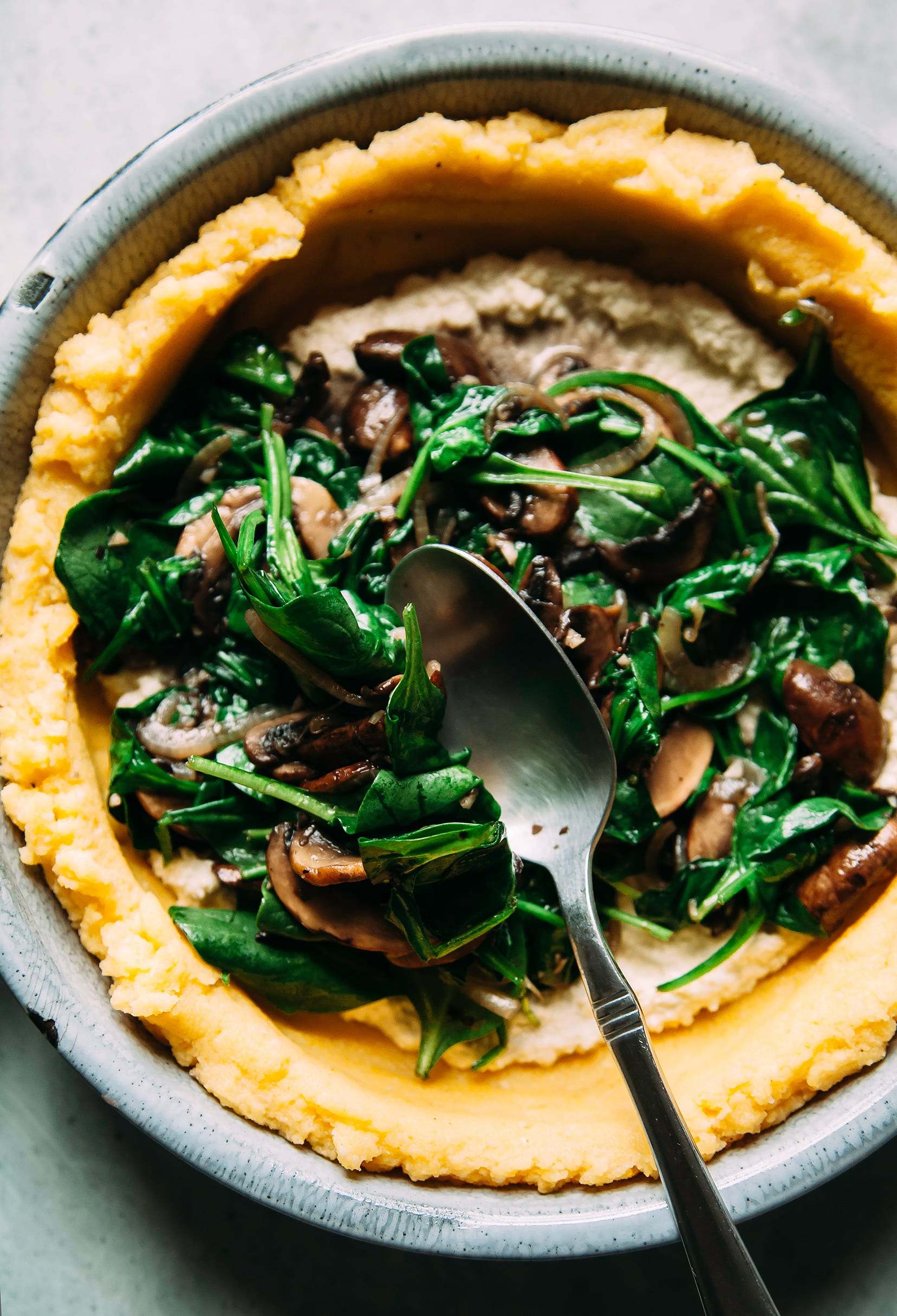 Image shows a spoon transferring a spinach and mushroom filling to a yellow polenta-based crust.