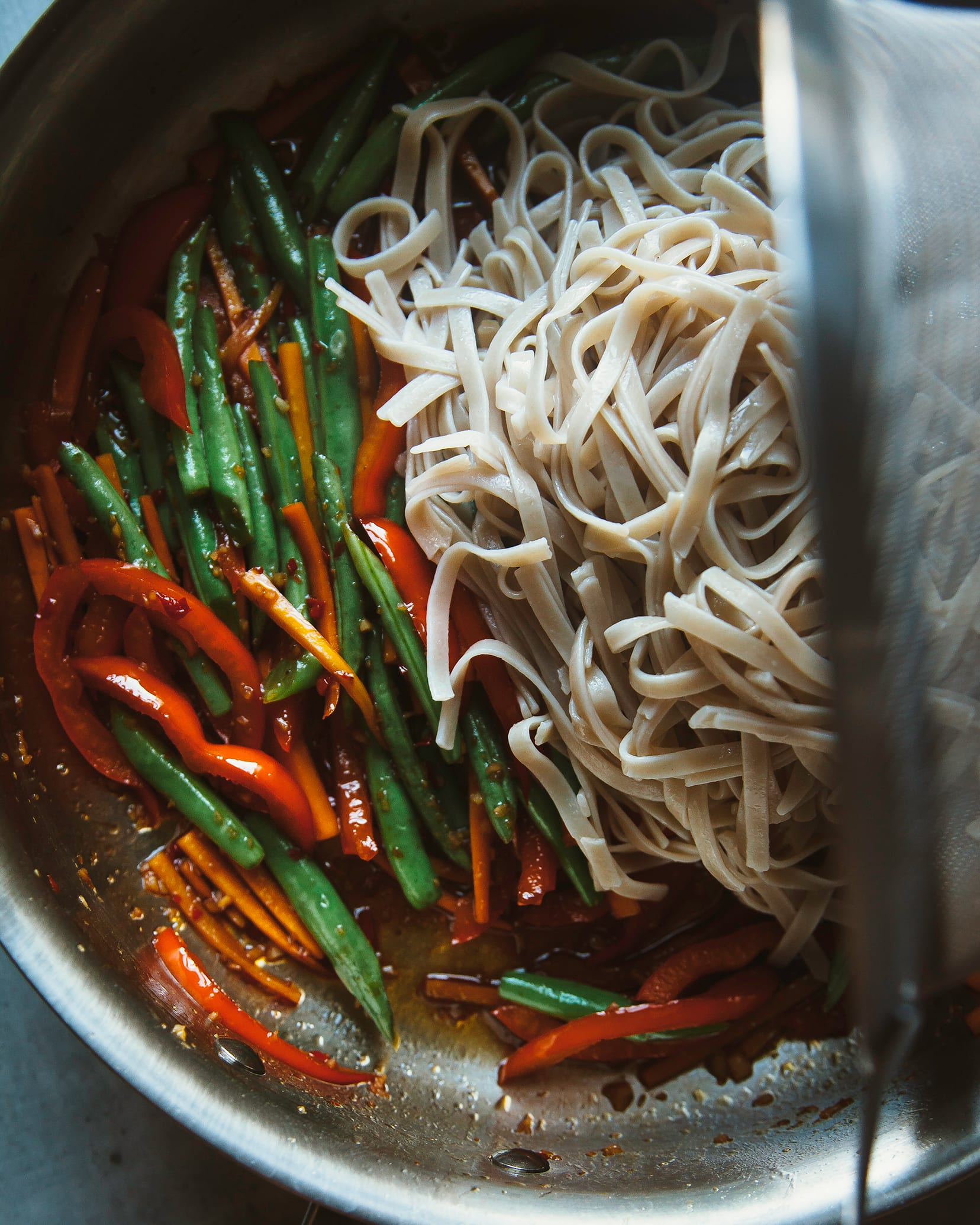 Image shows cooked noodles being added to a pan with sautéed vegetables.