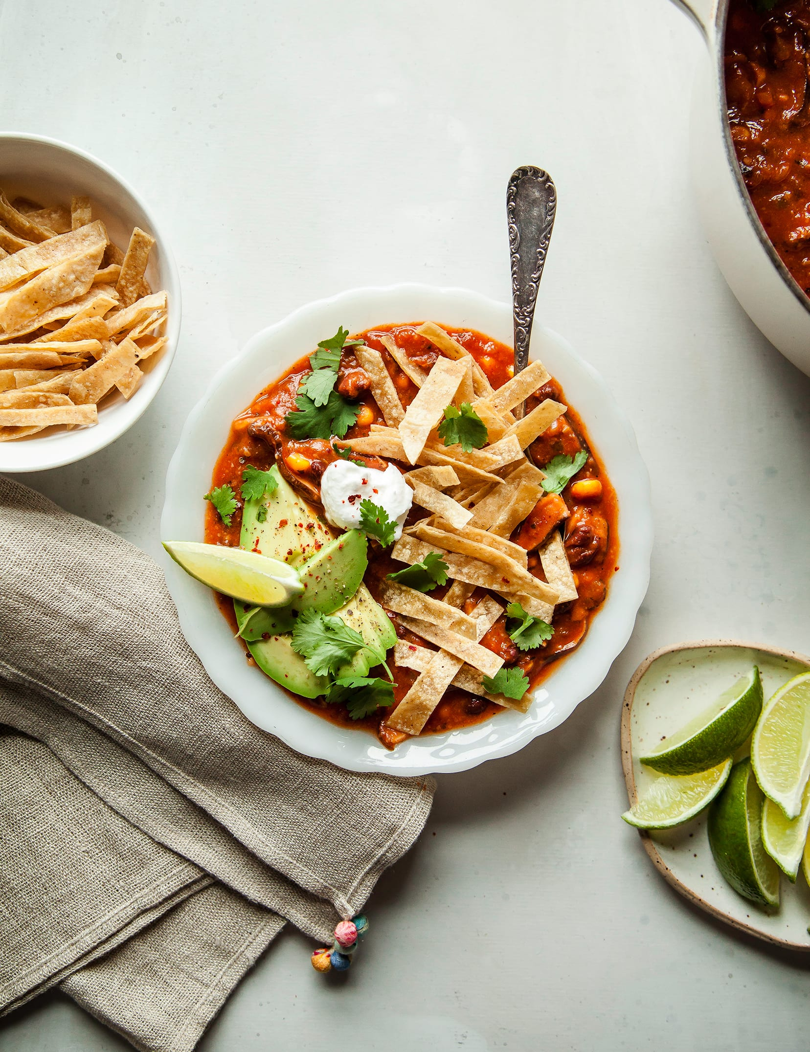 An overhead shot of smoky shiitake tortilla soup in a white bowl on a white background. The soup is topped with crispy tortilla strips, a lime wedge, vegan sour cream, and chopped cilantro.