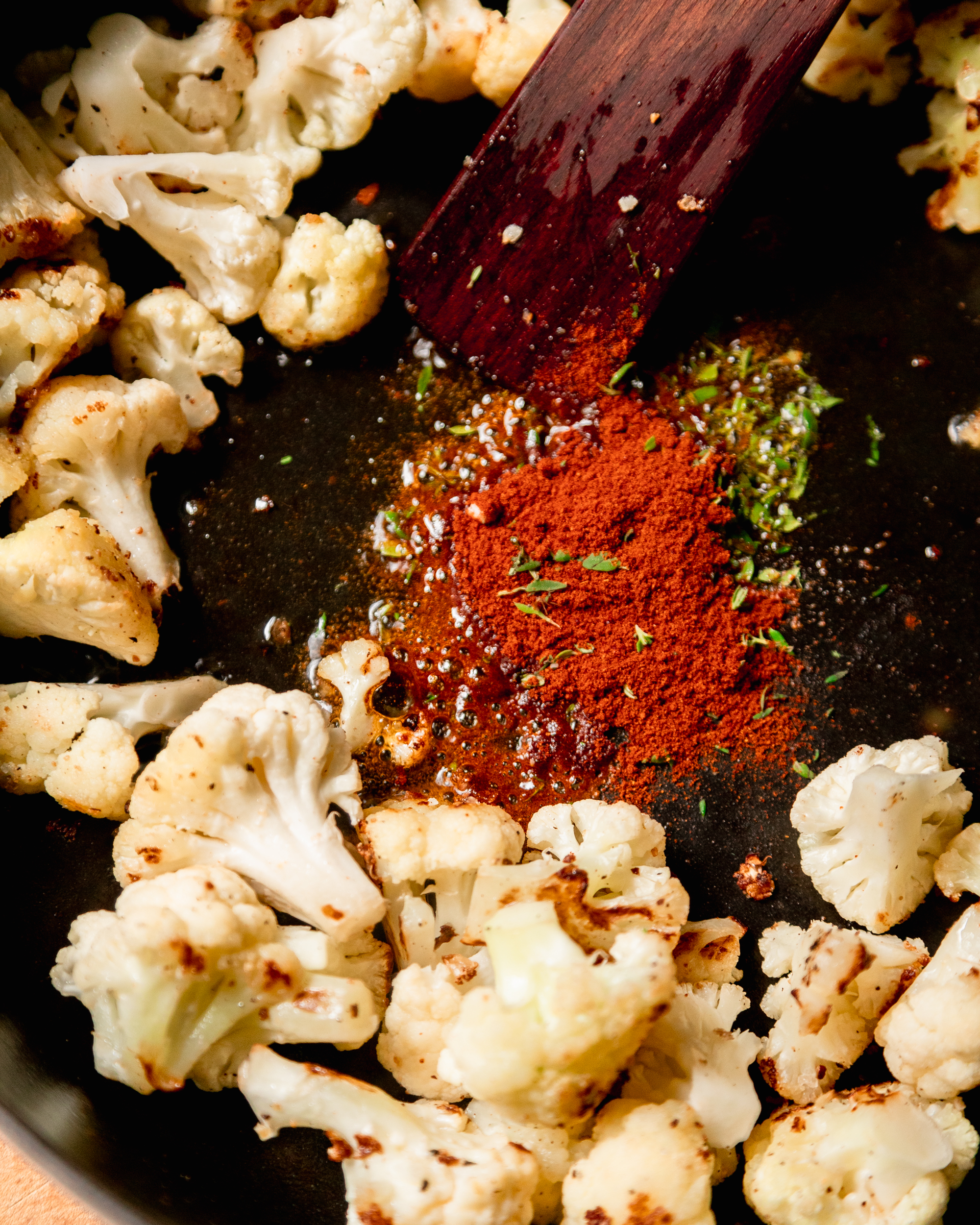 An up close shot of smoked paprika and thyme sizzling in hot oil, surrounded by cauliflower.