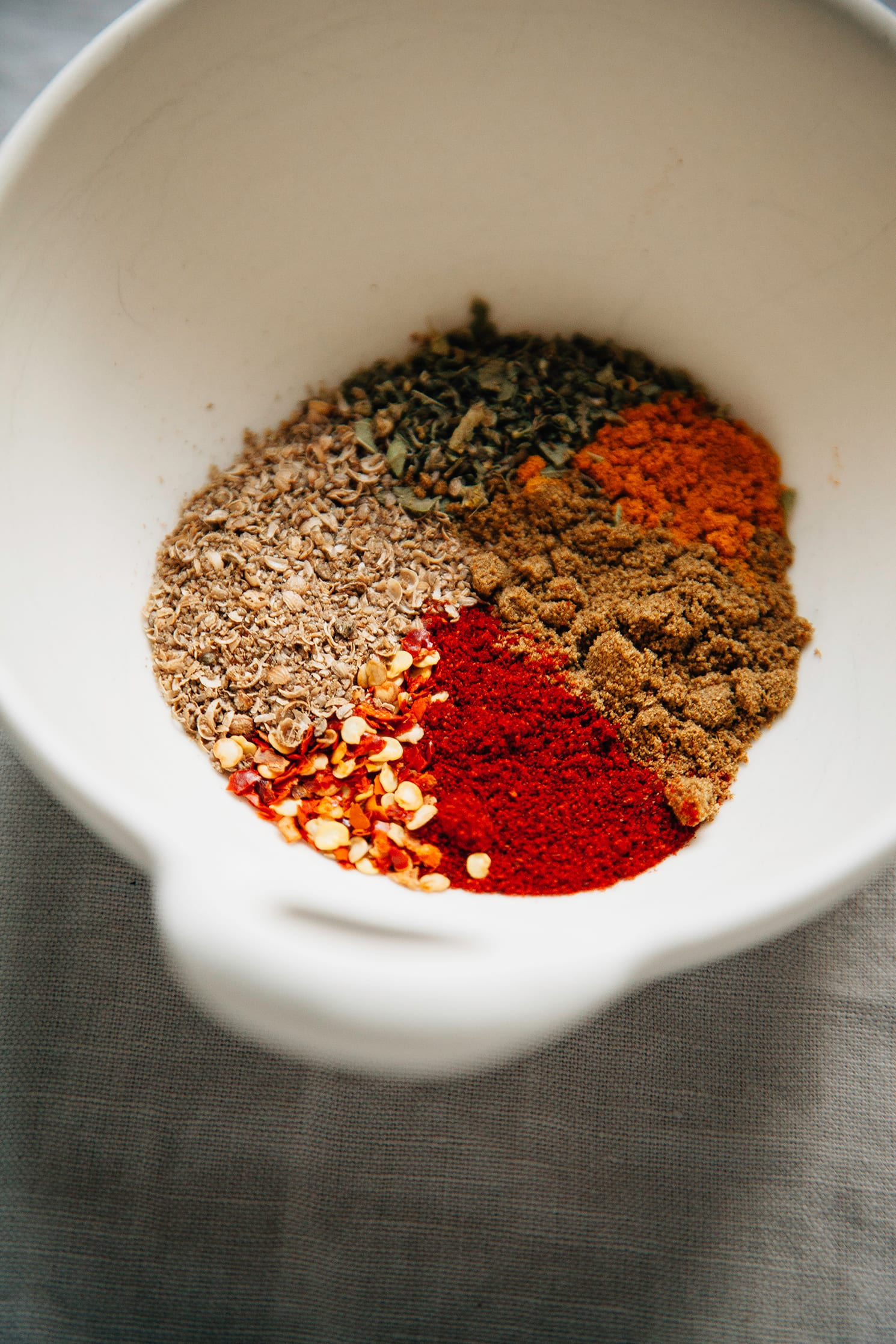 An up close shot of ground spices in a white bowl.