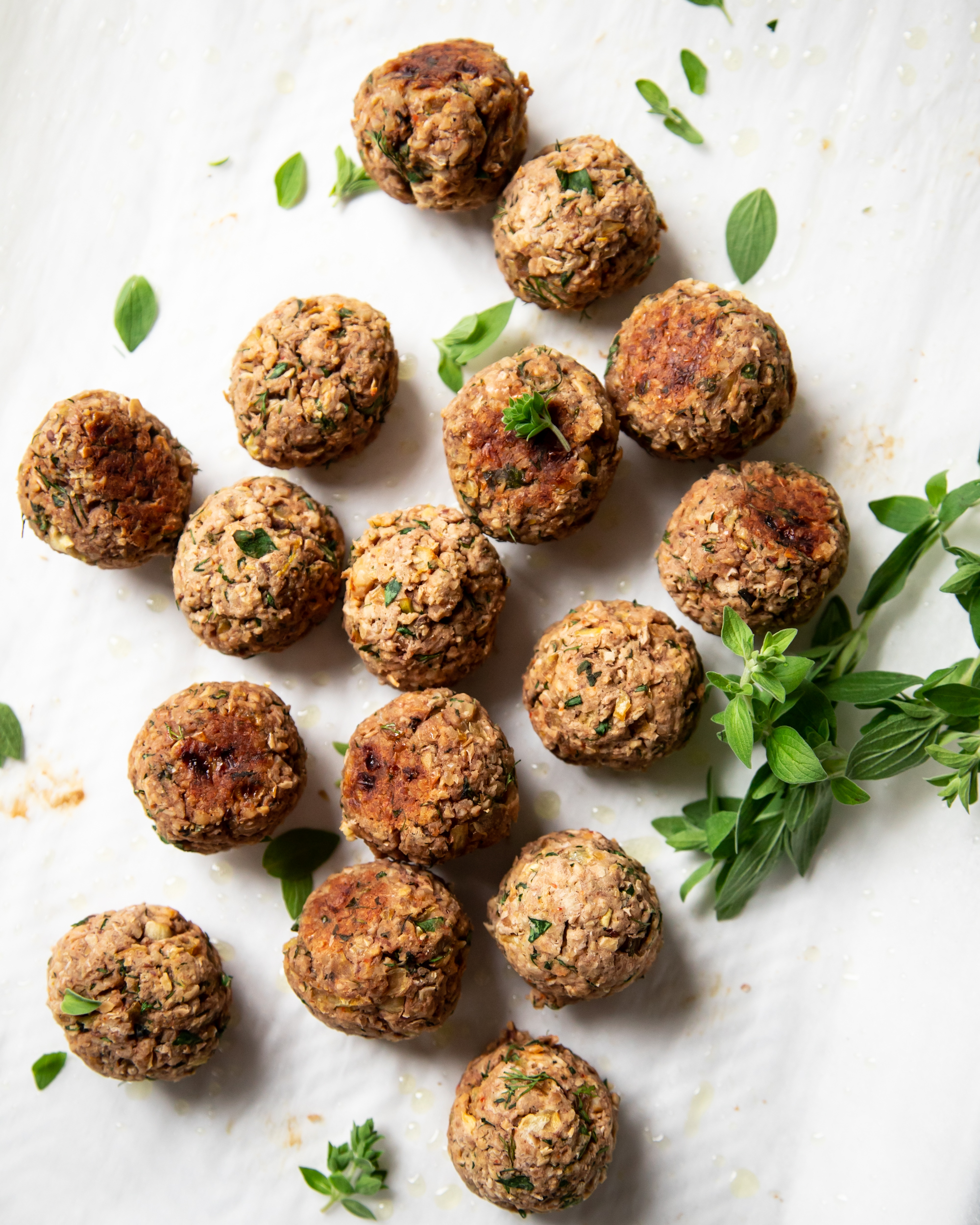 An overhead shot of cooked vegan meatballs, garnished with fresh oregano leaves.