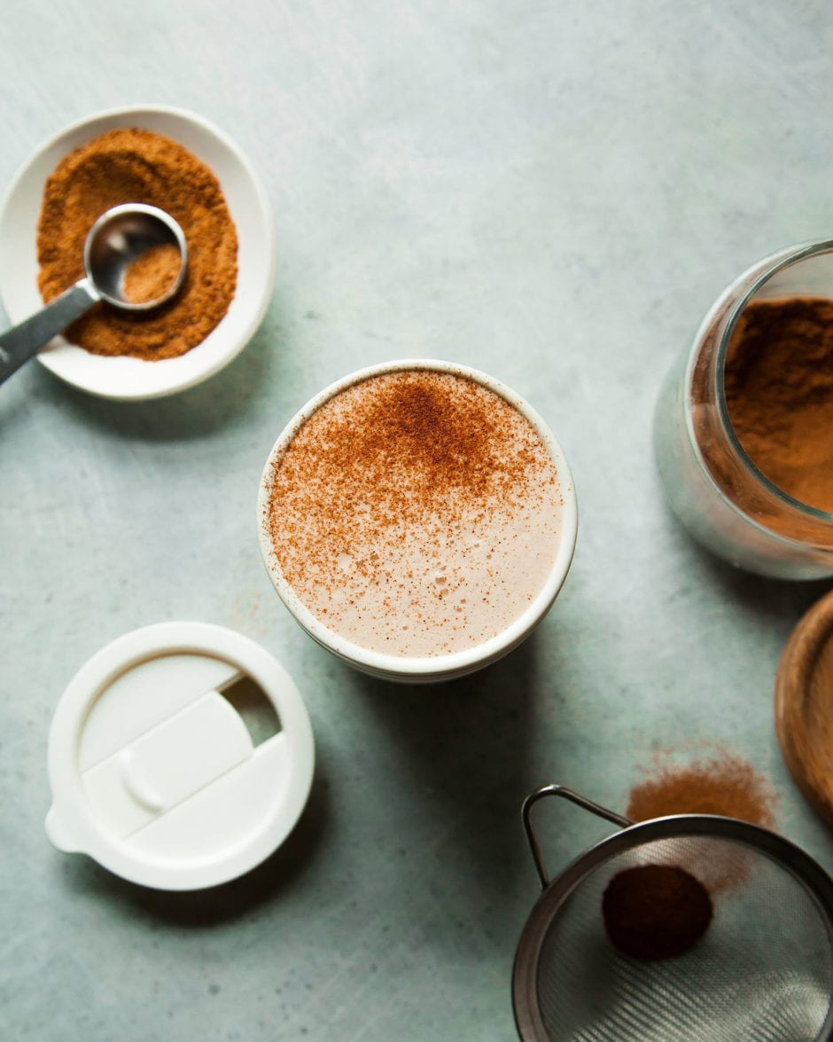 An overhead shot of a frothy tea latte in a white travel mug, dusted with cinnamon.