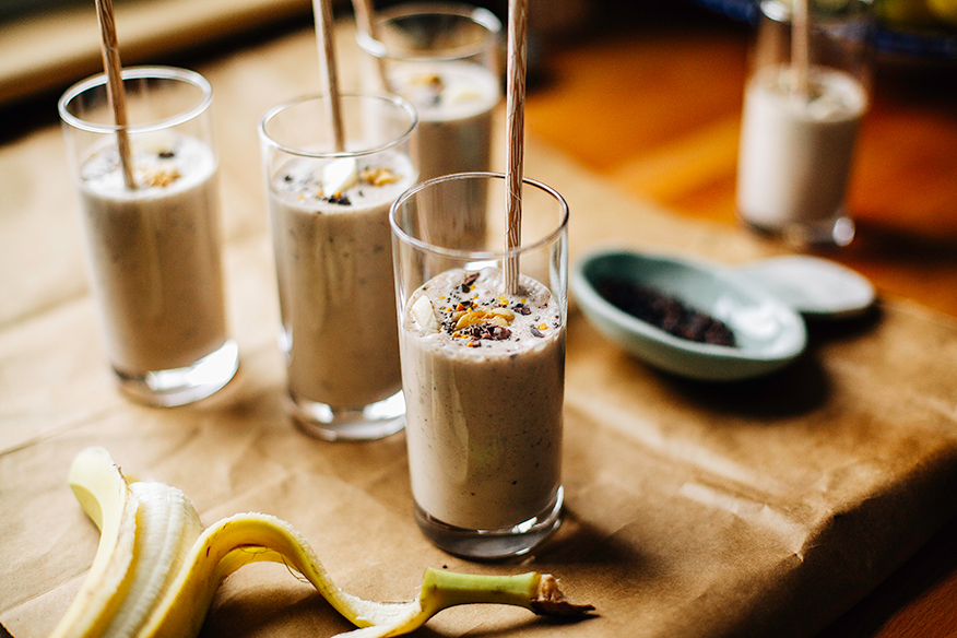 An head-on shot of several banana bread shakes in slim, clear glasses on a brown paper background. Shakes are garnished with sliced banana, walnuts, and cacao nibs and finished with beige paper straws.