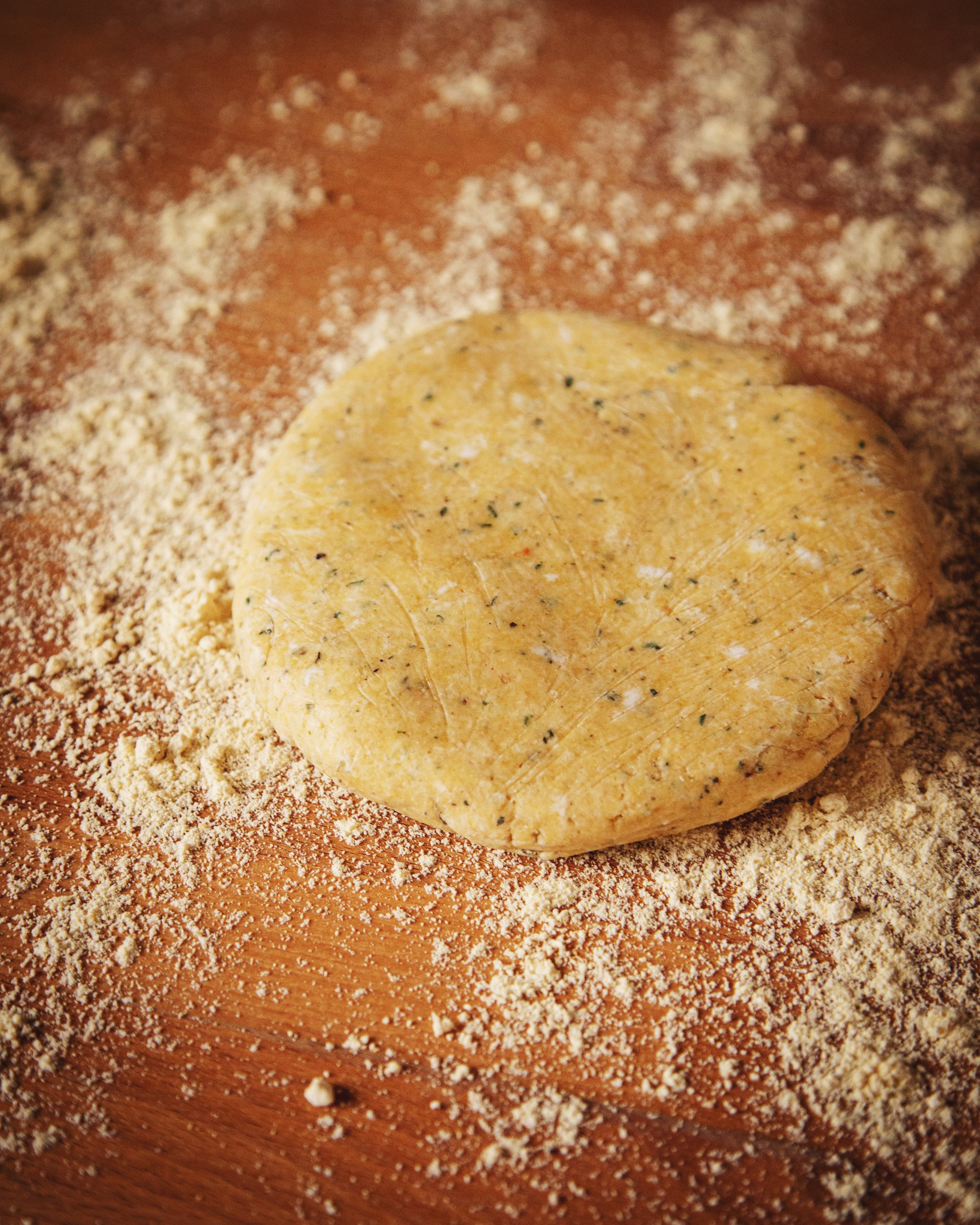 A disc of gluten-free black pepper galette dough. Flecks of pepper, herbs and vegan butter are visible. It is on a flour-dusted wood countertop.