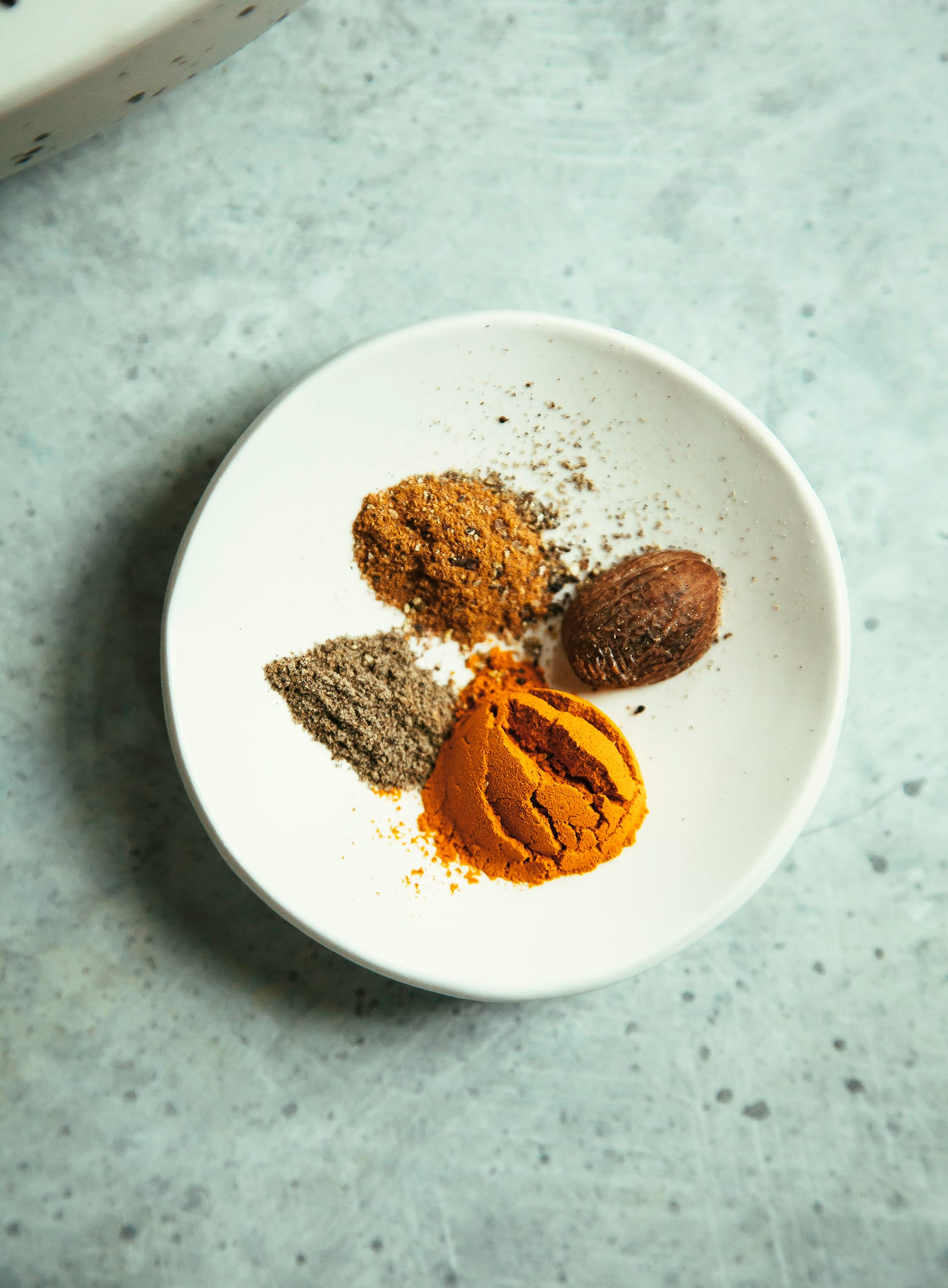 An overhead shot of spices in a small white bowl.